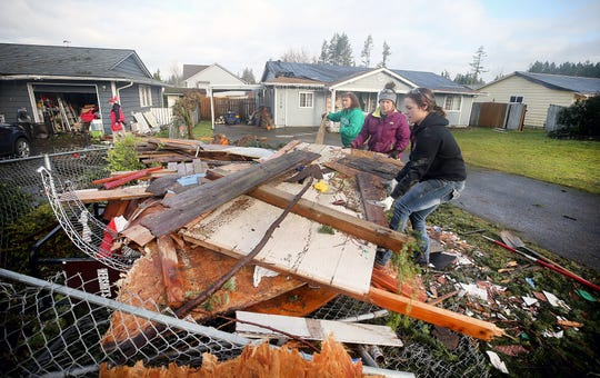 Volunteers Hollie Santos, right, and Sarah Kanyer, center, from Westcoast Fitness in Port Orchard, remove tornado debris on Thursday in Port Orchard.