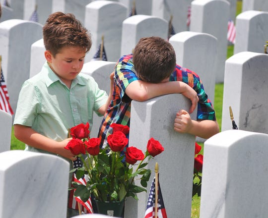Nicolas Amador comforts his brother Marcelo at their grandfather's grave during the 2018 Memorial Day observance at Canaveral National Cemetery in Scottsmoor.