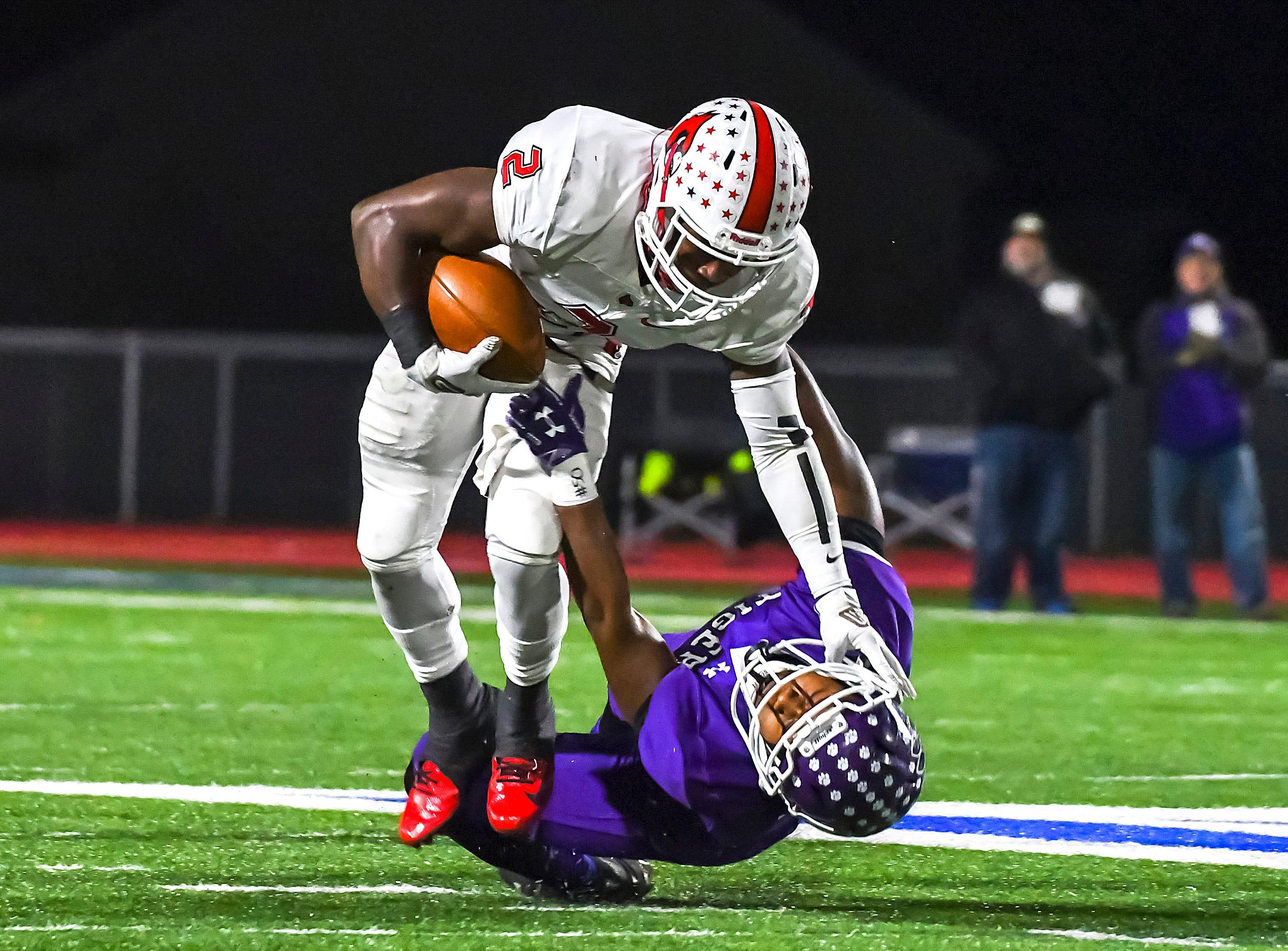 Colerain quarterback Deante Smith-Moore (2) stiff-arms a Pickerington Central defender in the OHSAA Region IV DI state semifinal at Piqua High School, Friday Nov. 23, 2018.