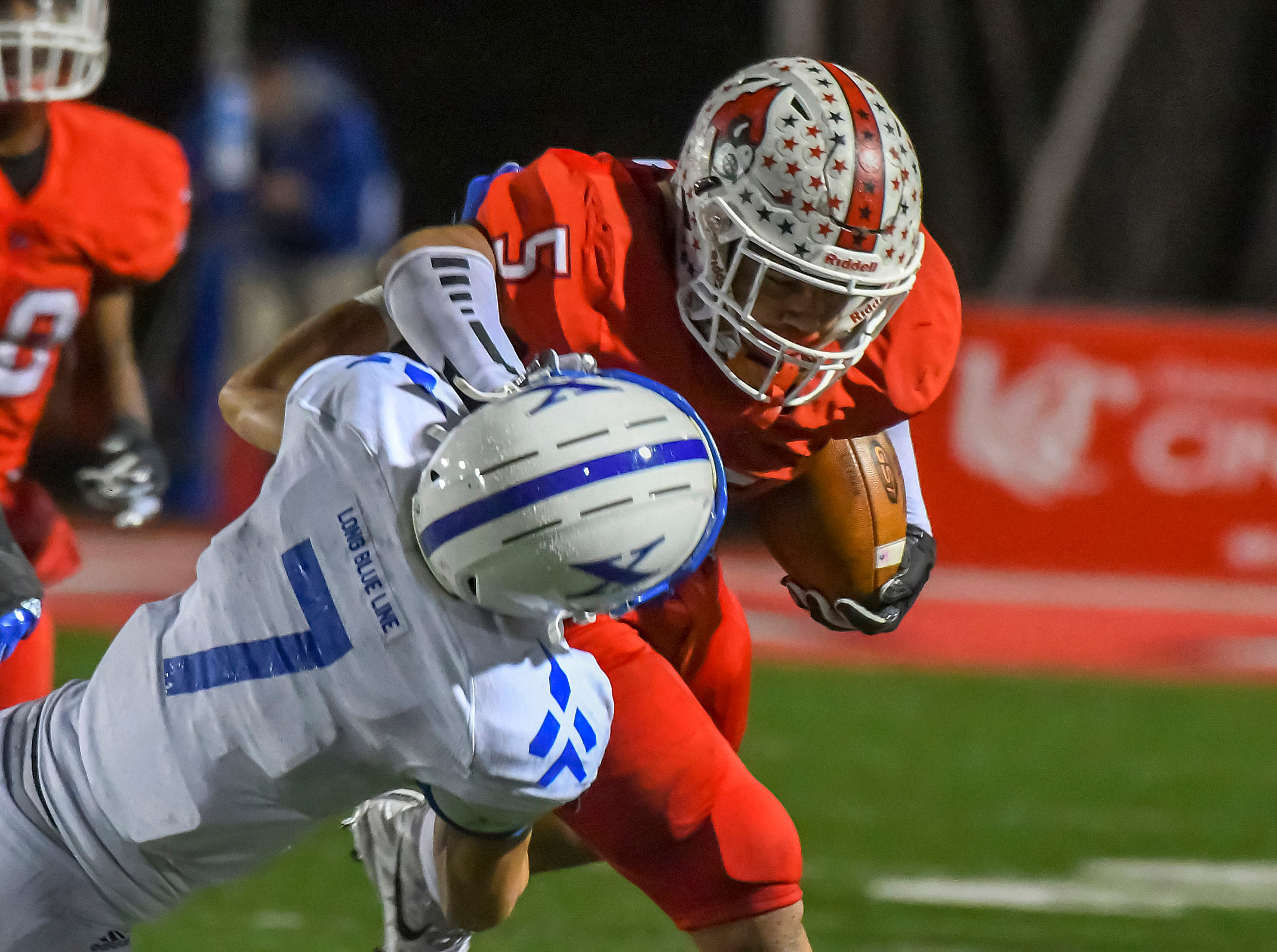 Ivan Pace Jr. of Colerain stiff arms St. Xavier defender Wiles Dolle (7) in the OHSAA DI Region IV playoffs at Colerain High School,  Friday Nov. 2, 2018
