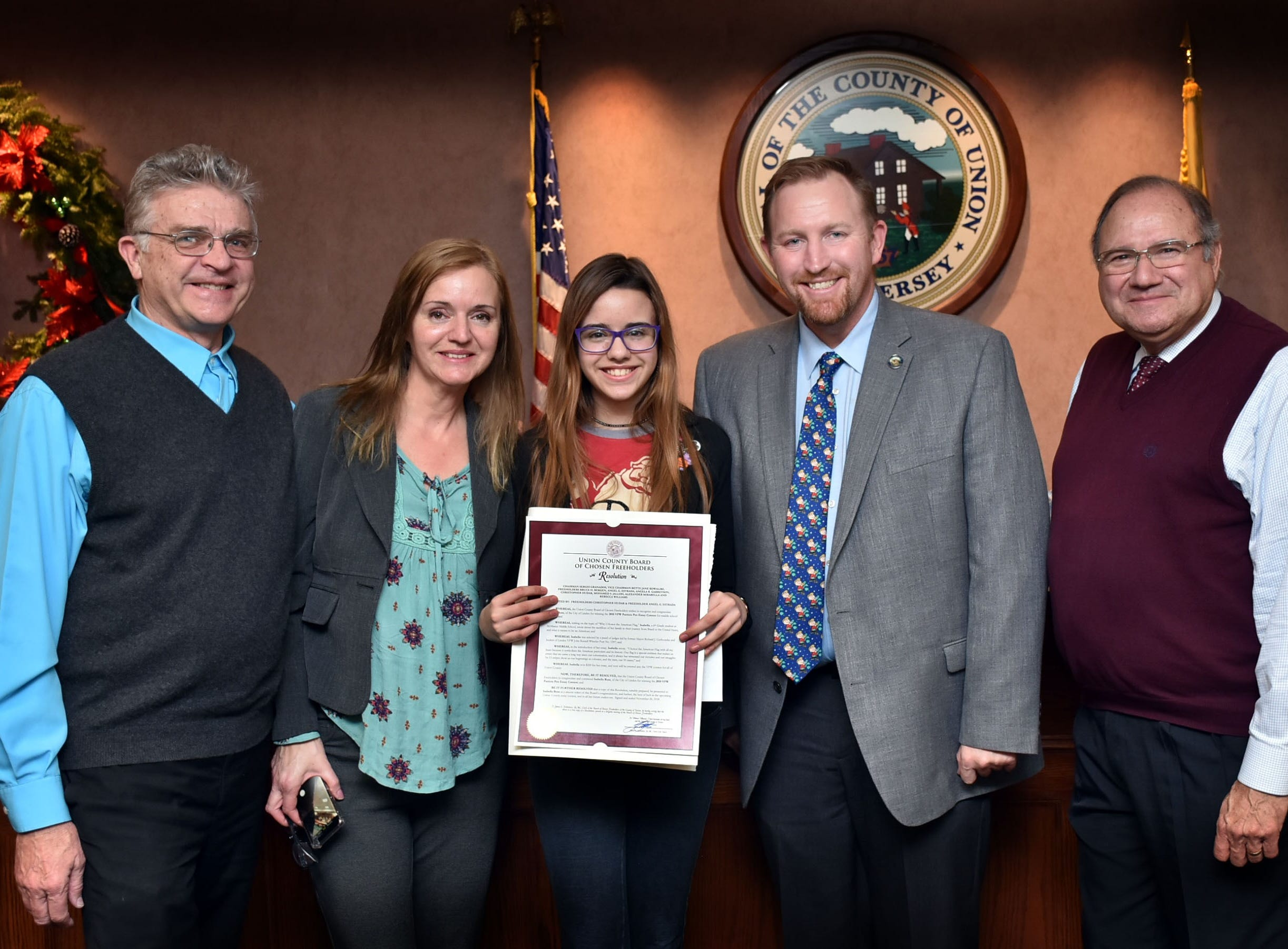 "Union County Freeholders Christopher Hudak and Angel G. Estrada present a resolution to Isabella Buss of Linden congratulating her on winning the 2018 Linden VFW John Russell Wheeler Post No. 1397 Patriots Pen Essay Contest for middle school students. They are joined by her parents Davi and Etel Buss. The topic of the contest was ""Why I Honor the American Flag."" Isabella, a 6th Grade student at McManus Middle School, wrote about the sacrifices of her family in their journey from Brazil to the United States, and what it means to be an American."