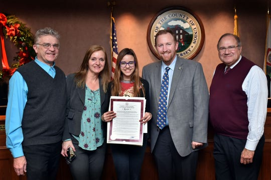 """Union County Freeholders Christopher Hudak and Angel G. Estrada present a resolution to Isabella Buss of Linden congratulating her on winning the 2018 Linden VFW John Russell Wheeler Post No. 1397 Patriots Pen Essay Contest for middle school students. They are joined by her parents Davi and Etel Buss. The topic of the contest was """"Why I Honor the American Flag."""" Isabella, a 6th Grade student at McManus Middle School, wrote about the sacrifices of her family in their journey from Brazil to the United States, and what it means to be an American."""