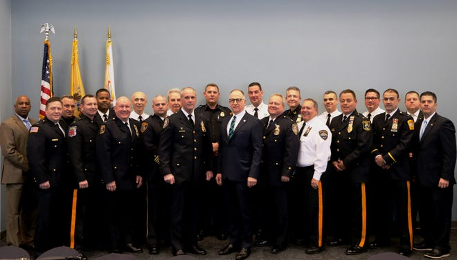 In announcement that Union county is slated to become the first in New Jersey fully patrolled by local agencies with full body-worn cameras pictured are back row (left to right): Plainfield Police Director Carl Riley, Springfield Police Chief John Cook, Roselle Police Chief Brian Barnes, Hillside Police Chief Vincent Ricciardi, Mountainside Police Officer-in-Charge Joseph Giannuzzi, Winfield Police Chief Walter Berg, Union County Sheriff Peter Corvelli, Kenilworth Police Chief John Zimmerman, Berkeley Heights Police Chief John DiPasquale, Scotch Plains Police Chief Theodore Conley, Kean University Police Director Mark Farsi.  And in front front row (left to right): Garwood Police Chief James Wright, Roselle Park Police Lt. David Pitts, Linden Police Chief David Hart, Westfield Police Chief Christopher Battiloro, Elizabeth Police Chief John Brennan, acting Union County Prosecutor Michael A. Monahan, Rahway Police Chief John Rodger, Union County Police Chief Chris Debbie, Fanwood Police Chief Richard Trigo, Clark Police Chief Pedro Matos, Union County Prosecutor's Office Chief of Detectives Vincent G. Gagliardi.