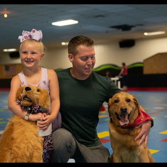 Jason Ogletree with his daughter, Ava, during her birthday this summer. Also pictured is Jake of Puppy Jake, a company dedicated to giving service dogs to vets.