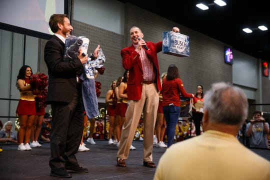 Iowa State Athletic Director Jamie Pollard hands Valero Alamo Bowl CEO Derrick Fox a case of Busch Light cans during the Cyclone Spirit Rally on Thursday, Dec. 27, 2018, in San Antonio. Iowa State takes on Washington State in the Valero Alamo Bowl on Friday.