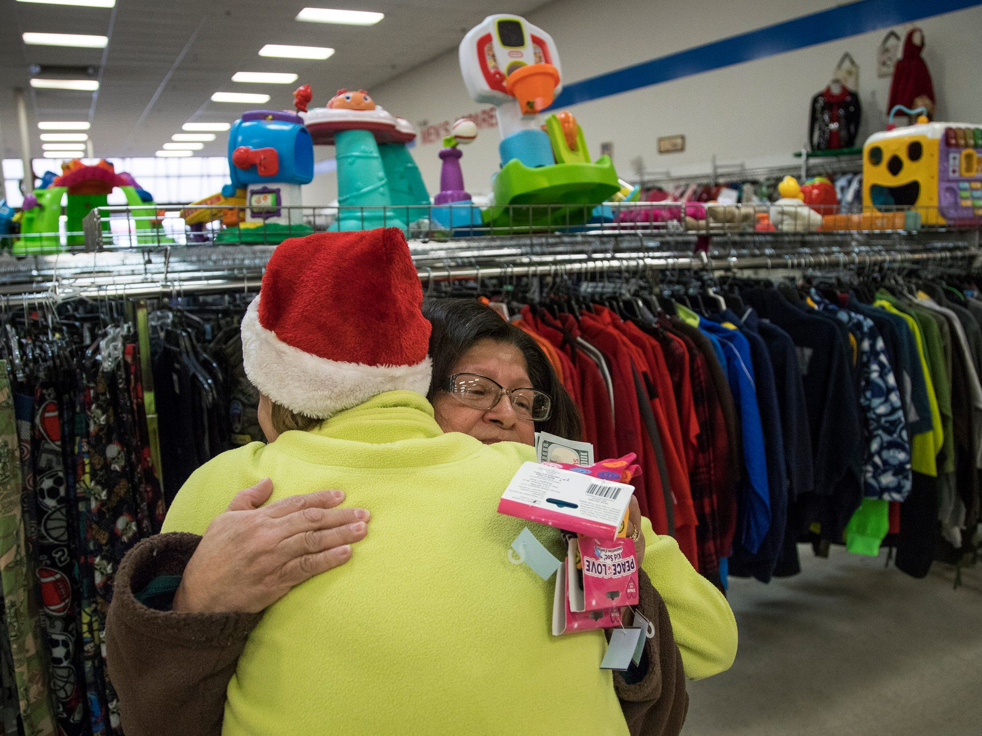 Azalia Smyth of Lincoln Park hugs Elf 32B after receiving cash from the Secret Santa at the Salvation Army in Lincoln Park, Friday Dec. 14, 2018.