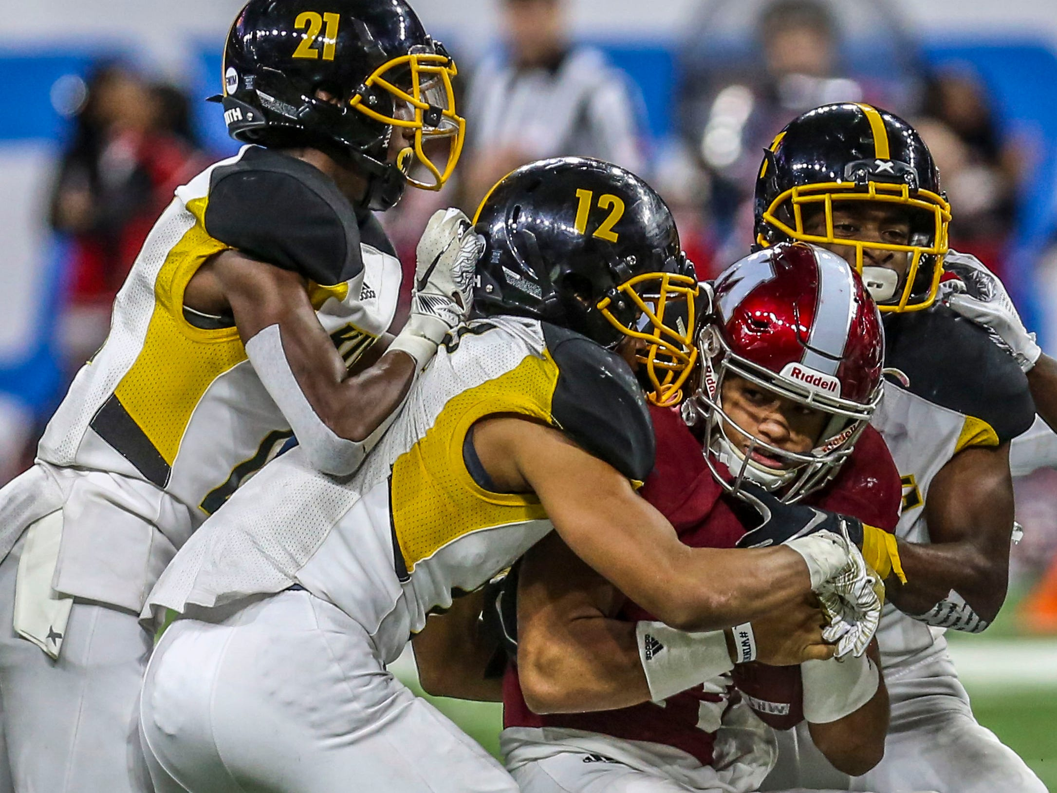 Muskegon Quarterback Cameron Martinez is tackled by Detroit Martin Luther King during the Division 3 MHSAA State Championship at Ford Field in Detroit on Saturday, Nov. 24, 2018.