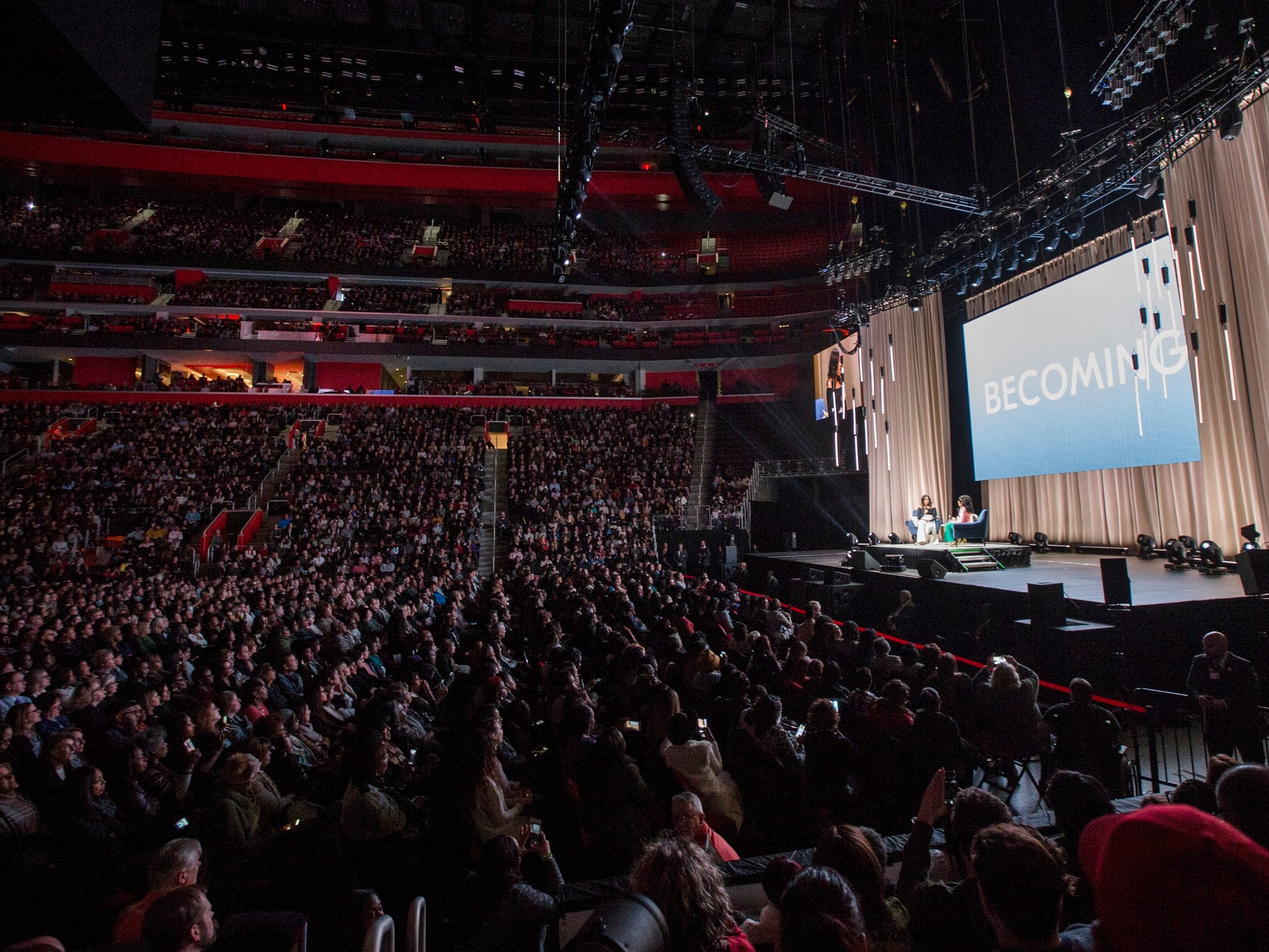 """Michelle Obama talks to comedian Phoebe Robinson on stage during her """"Becoming"""" book tour at the Little Caesars Arena in Detroit, Tuesday, Dec. 11, 2018."""