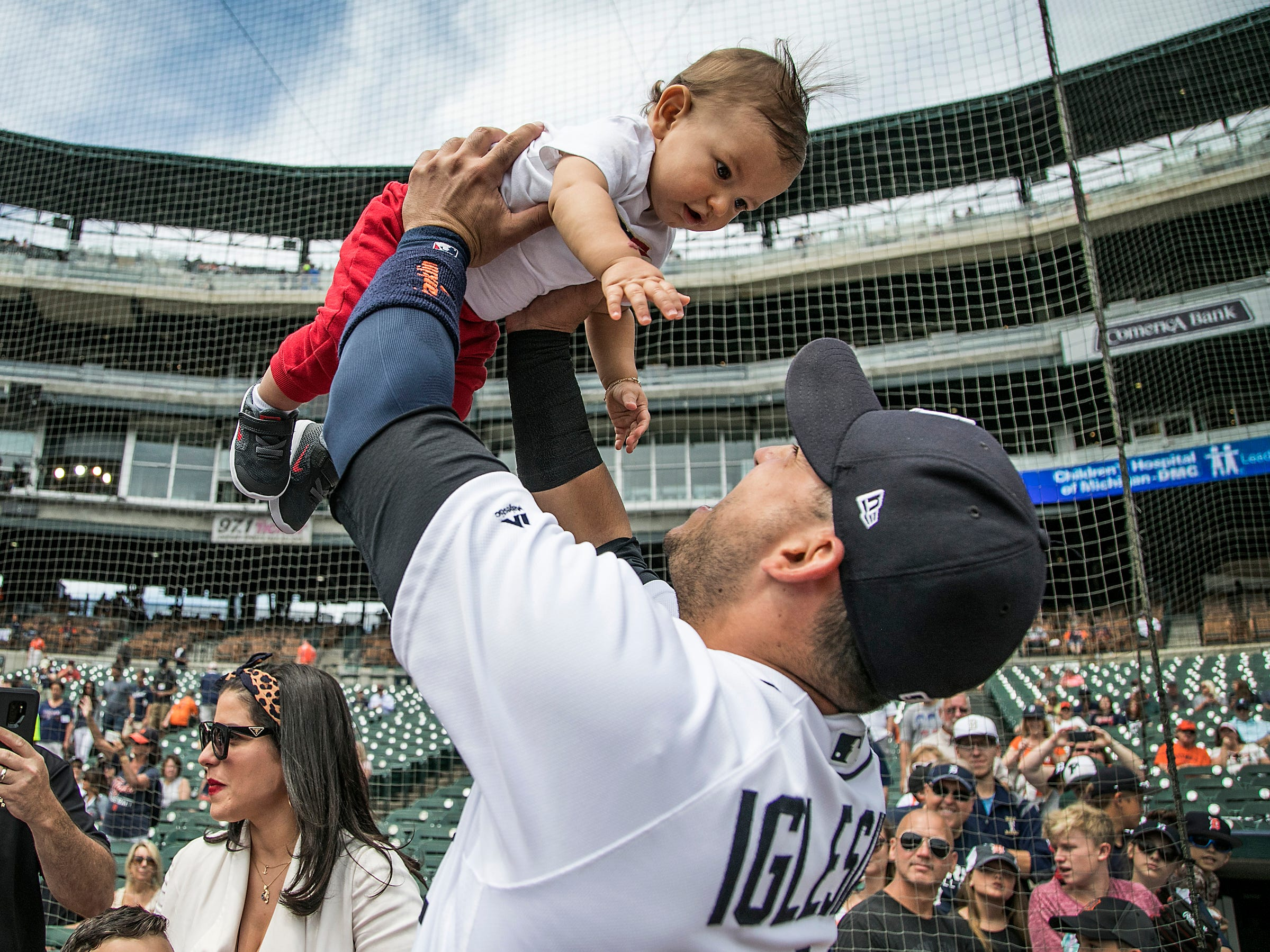Detroit Tigers Jose Iglesias holds up his 9-month-old son Alvaro before he is sworn in as American Citizens in a special ceremony held at Comerica Park in Detroit Monday, June, 25, 2018, before the Tigers took on the A's.