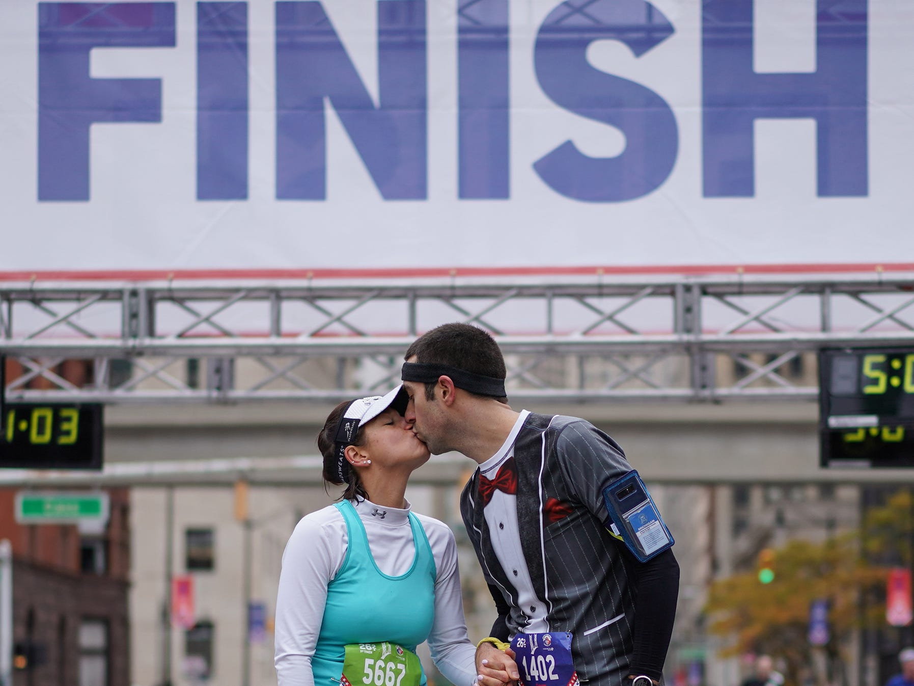 Newlyweds Whitney Black of Kentwood, MI and Steven Phillips of Kentwood share a kiss at the finish line for cameras after finishing the 41st Annual Detroit Free Press/Chemical Bank Marathon in Detroit on Sunday, Oct. 21, 2018. The couple got married during the race.