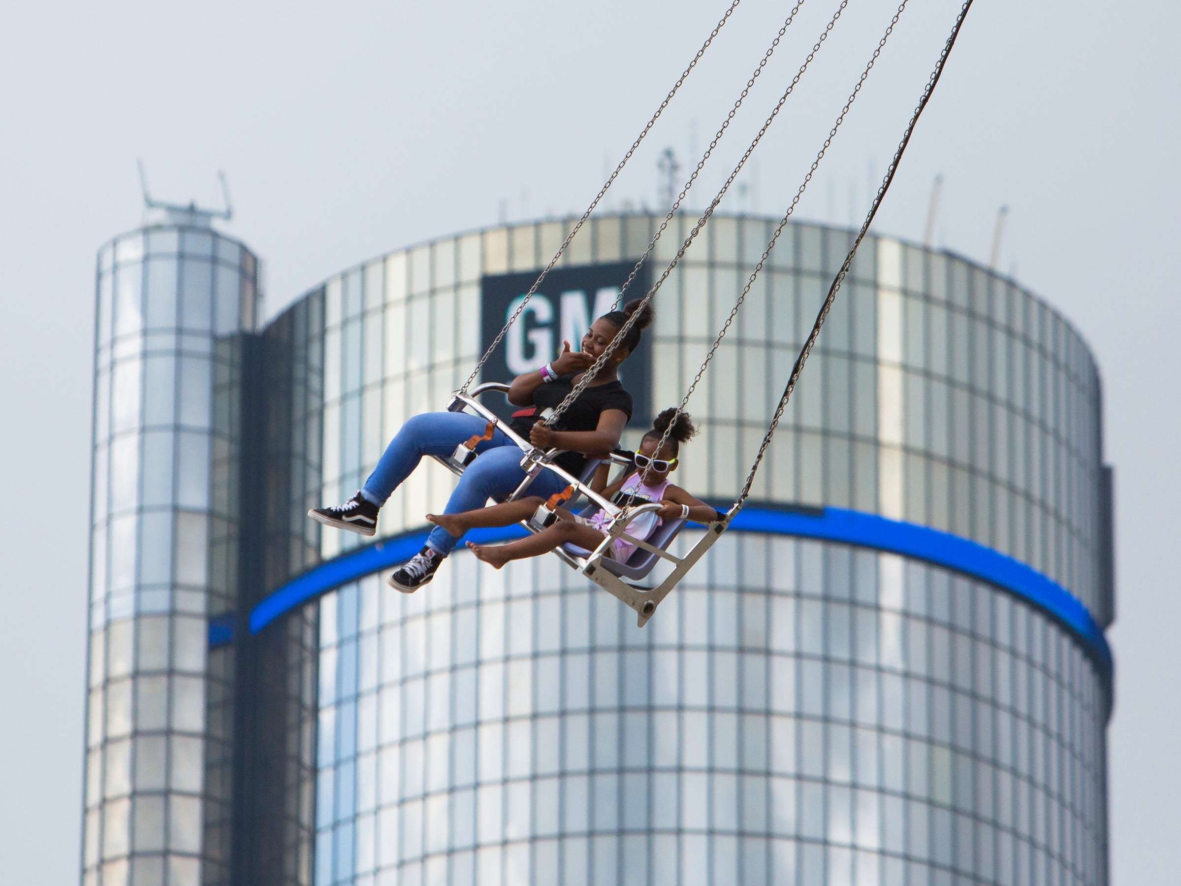 Karisma Coleman, 13, of Detroit, rides the swings with her sister Kimarie, 6 during GM River Days at the Detroit Riverfront in Detroit on June 23, 2018.
