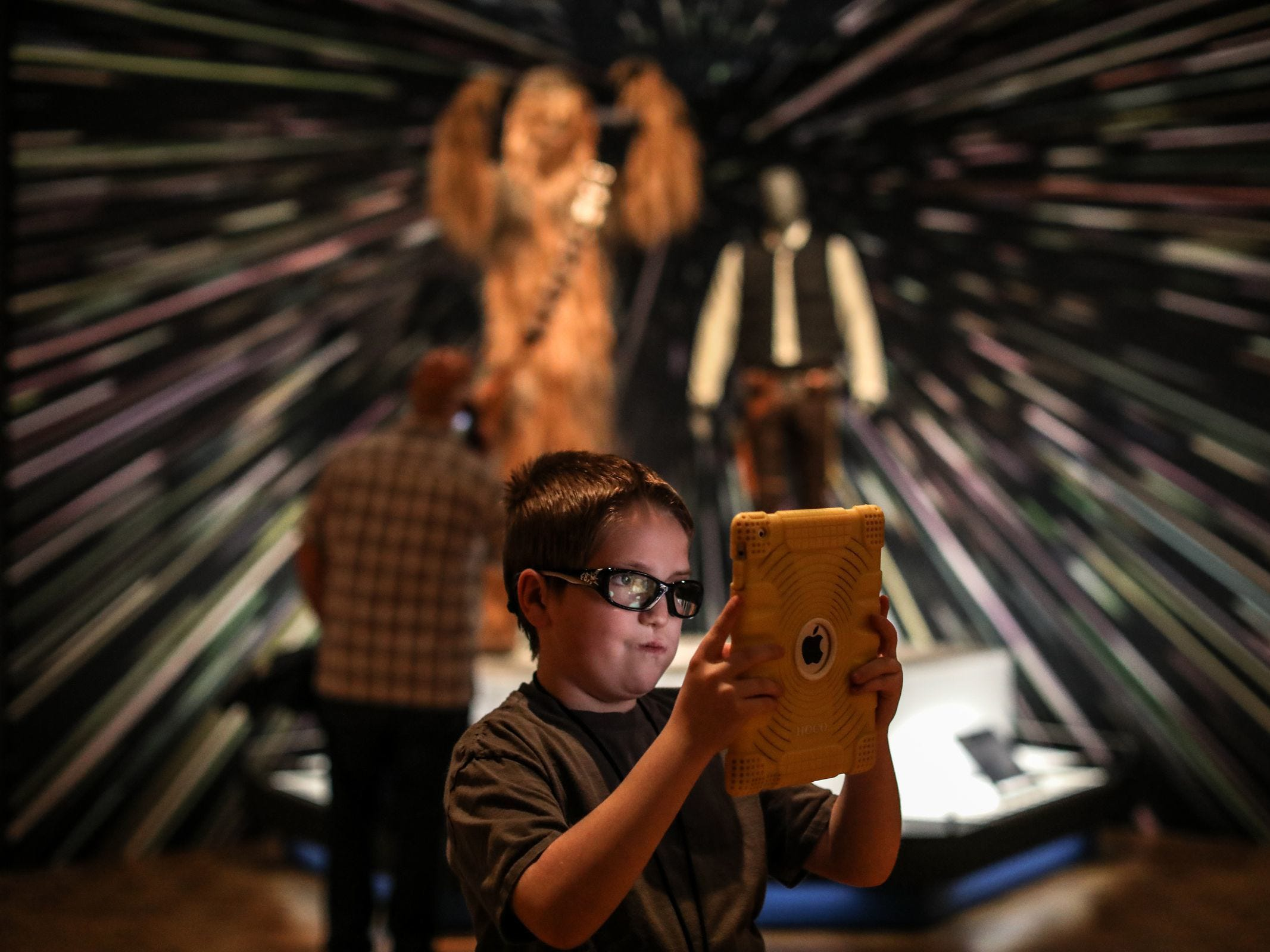 "Rian McGrail, 10, of Warren takes a selfie his iPad with the Chewbacca and Han Solo costumes in the background during the member's preview of ""Star Wars and the Power of Costume"" show at the Detroit Institute of Arts in Detroit on Saturday, May 19, 2018."