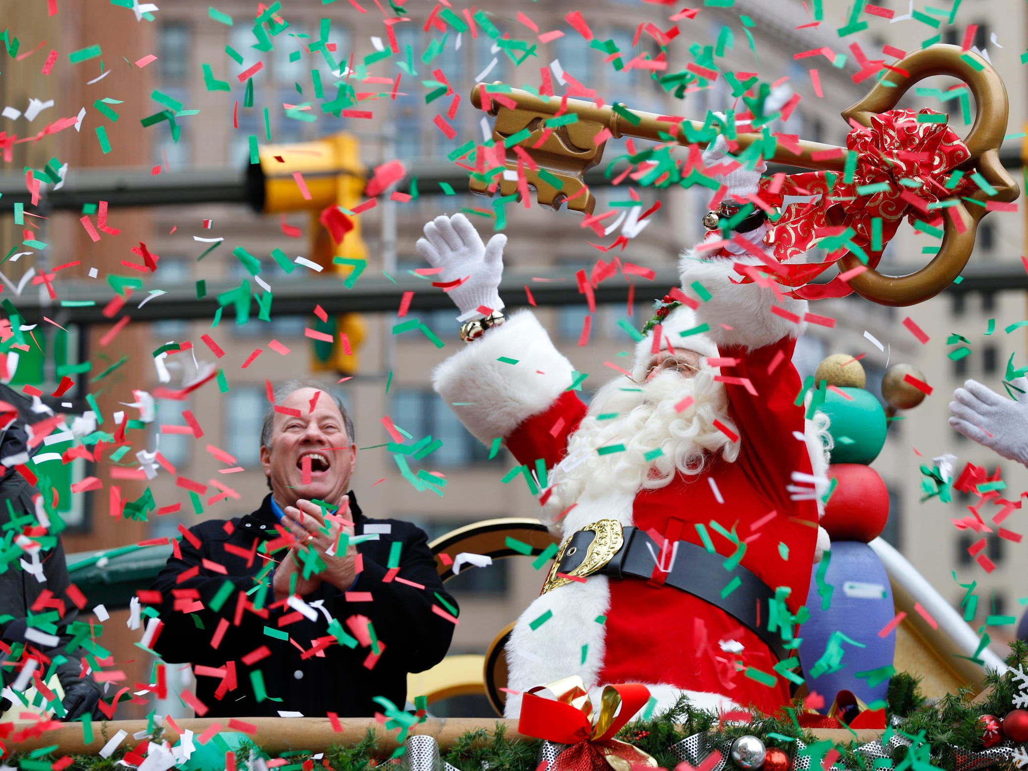 Santa Claus gets the key to the city from Detroit Mayor Mike Duggan during the 92nd America's Thanksgiving Day Parade on Woodward Avenue in Detroit, Thursday, Nov. 22, 2018.