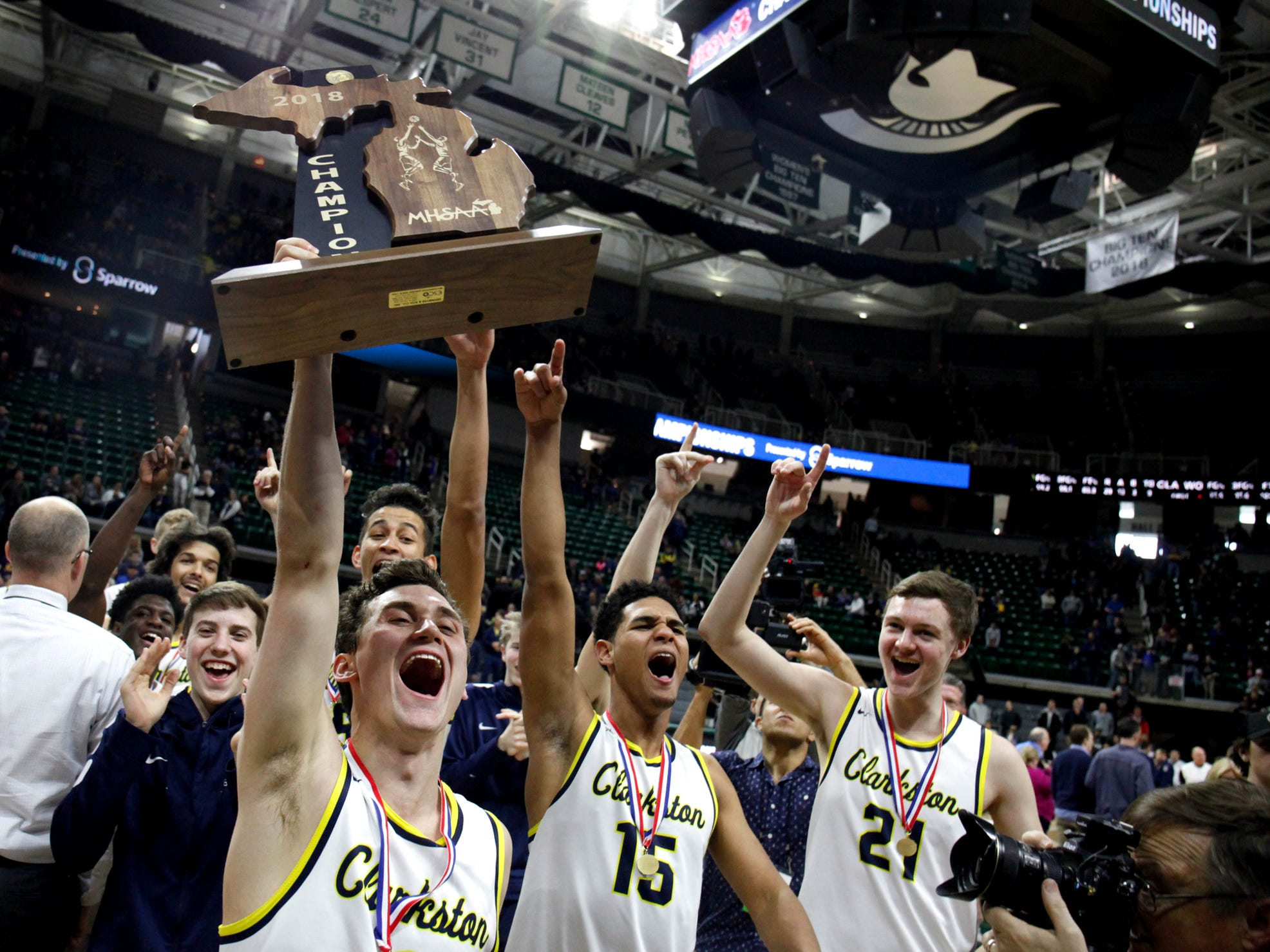 Clarkston guard Foster Loyer and his teammates celebrate the 81-38 win against Holland West Ottawa in the Class A MHSAA Championship Saturday, March 24, 2018, at the Breslin Center in East Lansing MI.