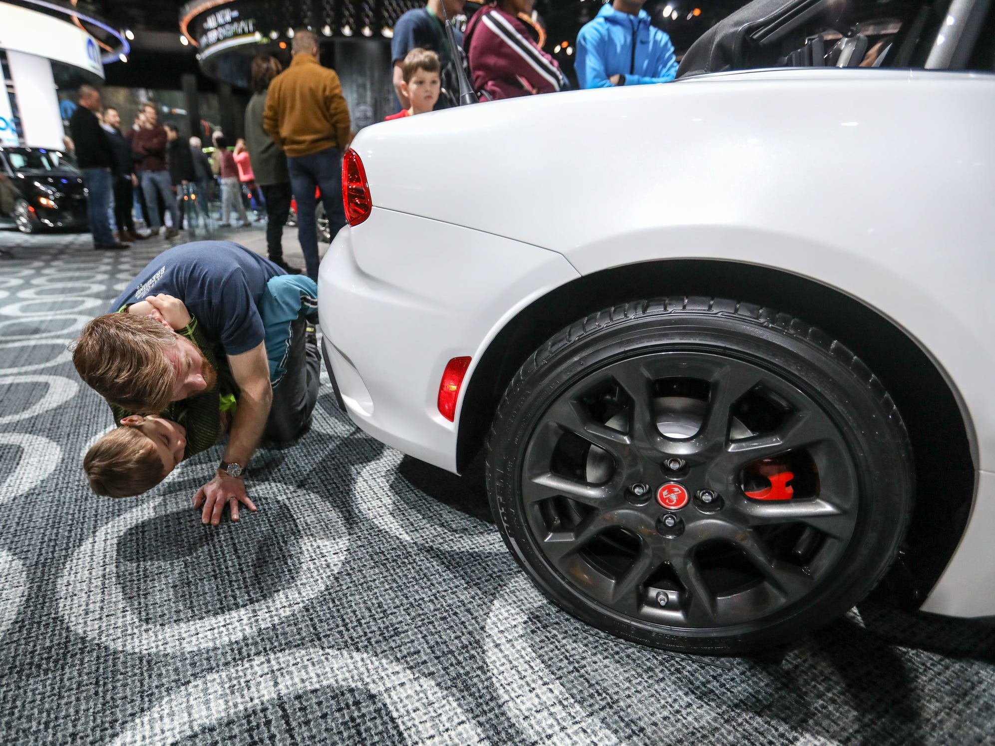 Kevin Mount, 39, of Yplsilanti checks out the suspension and drive train of the 2018 FIAT 124 Spider, with his son, Issac, 4, during the first public day of the North American International Auto Show in downtown Detroit on Saturday, Jan. 20, 2018.