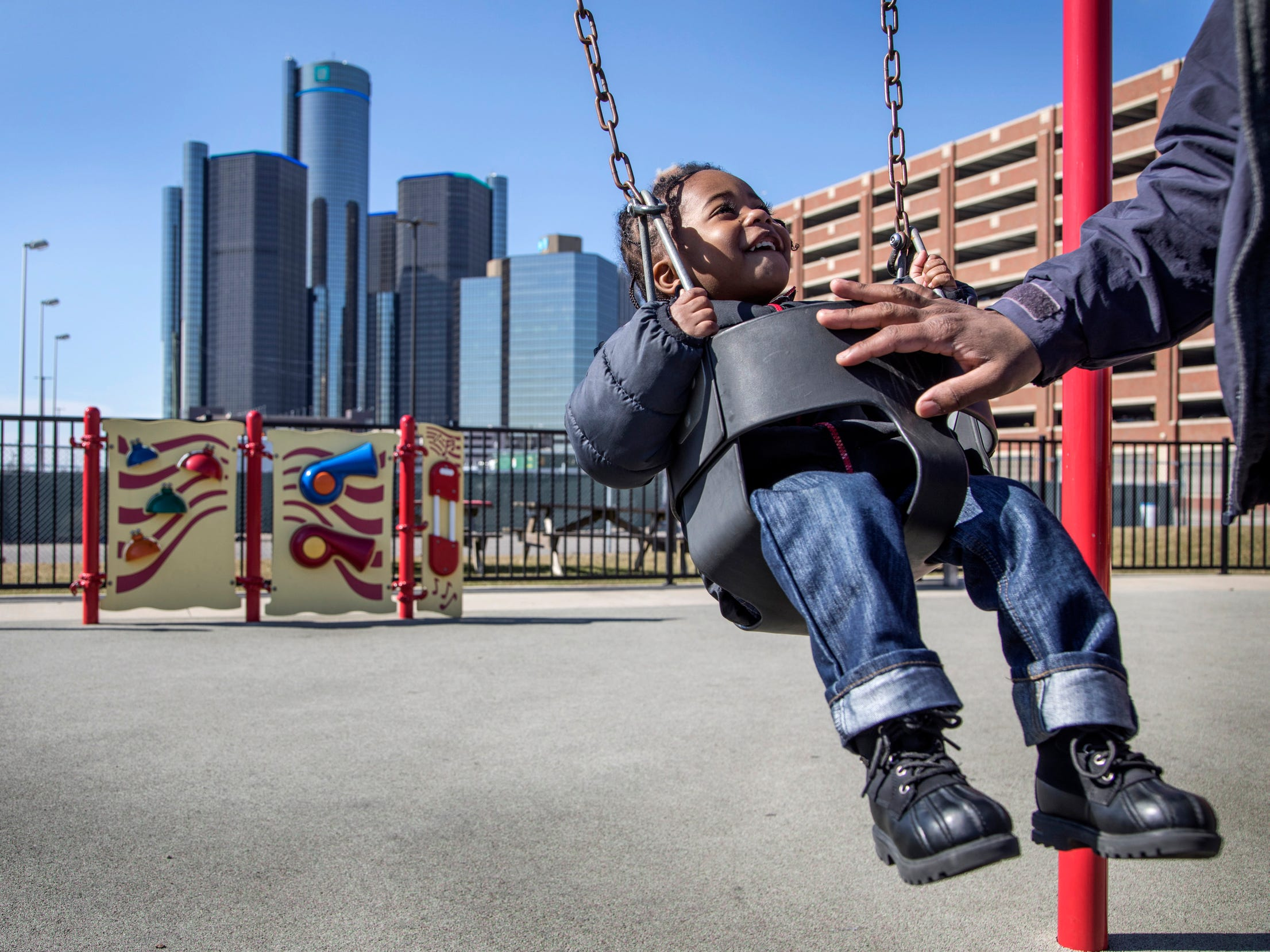 With near 60 degree temperatures Thomas King Jr. 2, of Detroit, smiles as he gets a push on the swing from his father Thomas King Sr. 25, as metro Detroiters enjoy the Detroit River Front Tuesday Feb. 27, 2018.