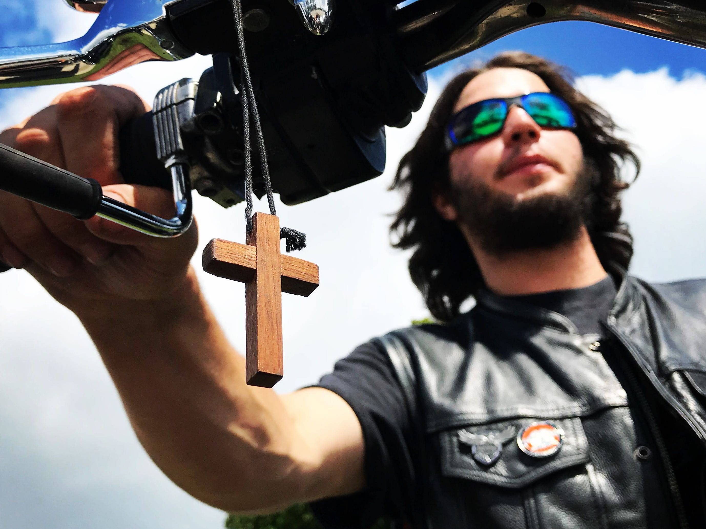 "Nicholas Roselli, 26, of Manchester, New Hampshire, by way of Sturgis, South Dakota, where a stranger gave him a crucifix he now hangs on the throttle side of his 1995 1250 Harley Davidson Sportster, arrives at Veterans Park in Milwaukee for the Harley-Davidson 115th anniversary. ""I love riding,"" said Roselli who was diagnosed with multiple sclerosis three years ago. ""It is my dream to travel the whole country."""