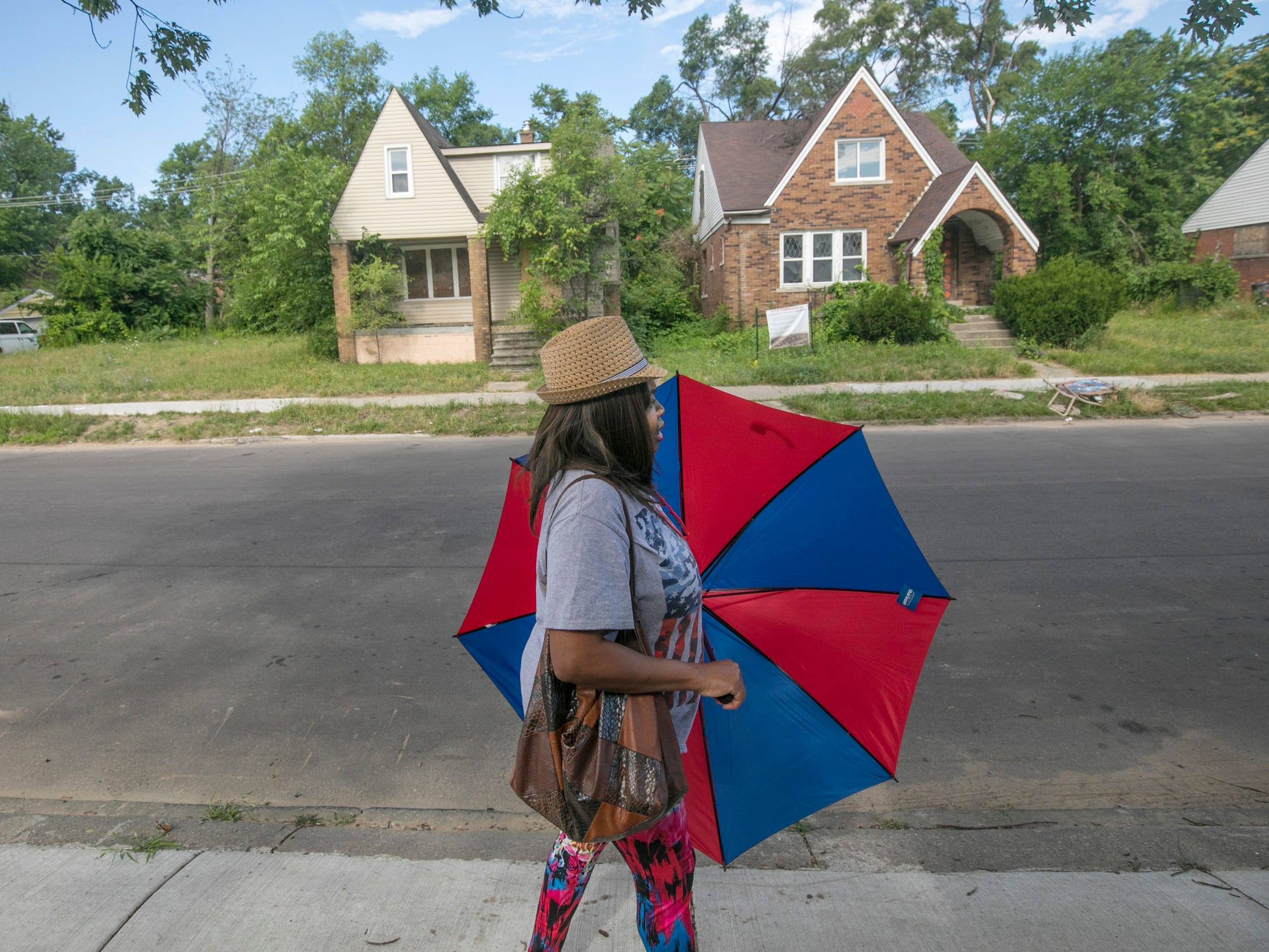 Renee Jones, 49, of Woodingham Drive in Detroit said she would be more inclined to stay in the neighborhood if some of the abandoned homes would get renovated as she walks by two slated homes as part of the Fitzgerald neighborhood revitalization project Thursday, July 5, 2018.