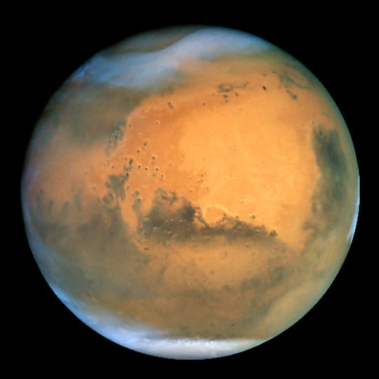 In an image that scientists call the sharpest image ever made from Earth, the planet Mars is seen as a dynamic planet covered by frosty white water ice clouds and swirling orange dust storms above a vivid rusty landscape, in this view made by the Earth-orbiting Hubble Space Telescope on June 26, 2001.