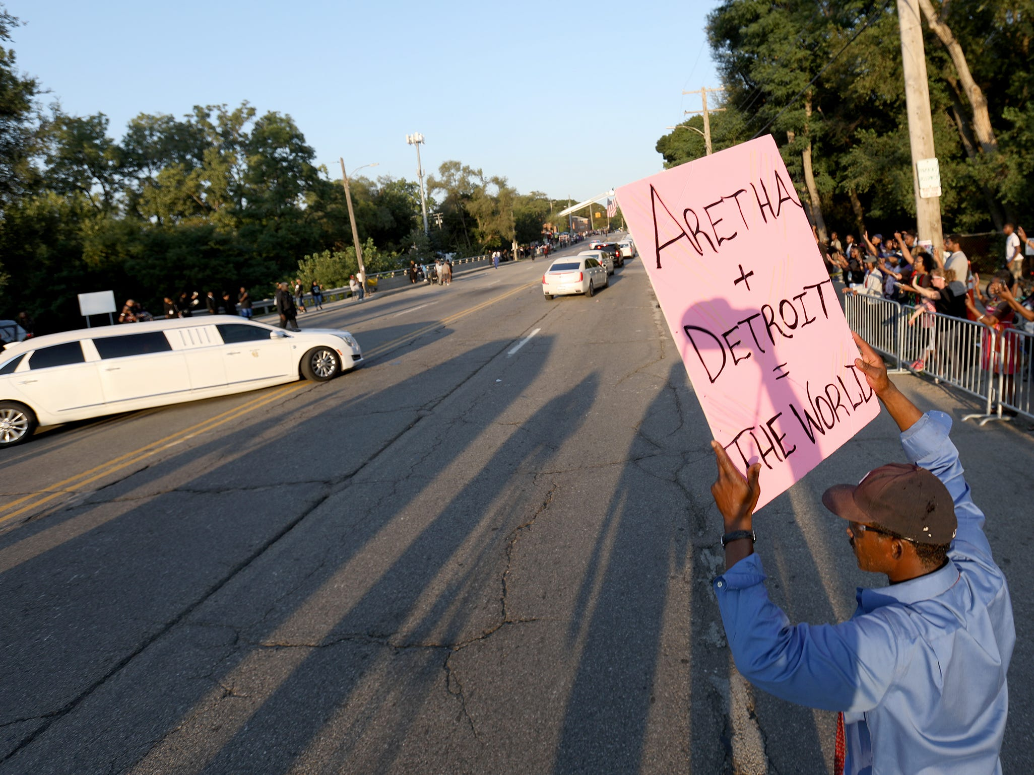 Robbie Hayes, 49, of Detroit waves a sign of support for Aretha Franklin as the processional leaves  Greater Grace Temple to her final resting place at Woodlawn Cemetery in Detroit, Friday, August 31, 2018.