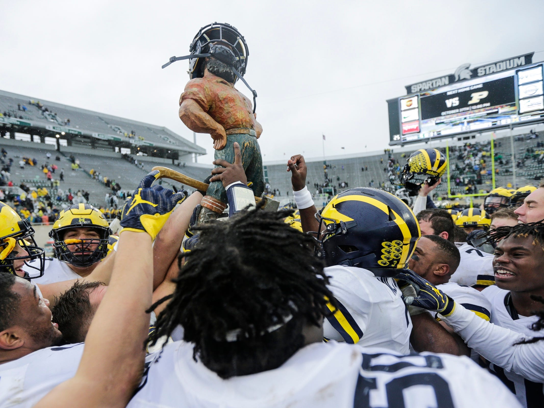 Michigan players raise the Paul Bunyan trophy to celebrate their 21-7 victory over Michigan State at Spartan Stadium in East Lansing, Saturday, October 20, 2018.