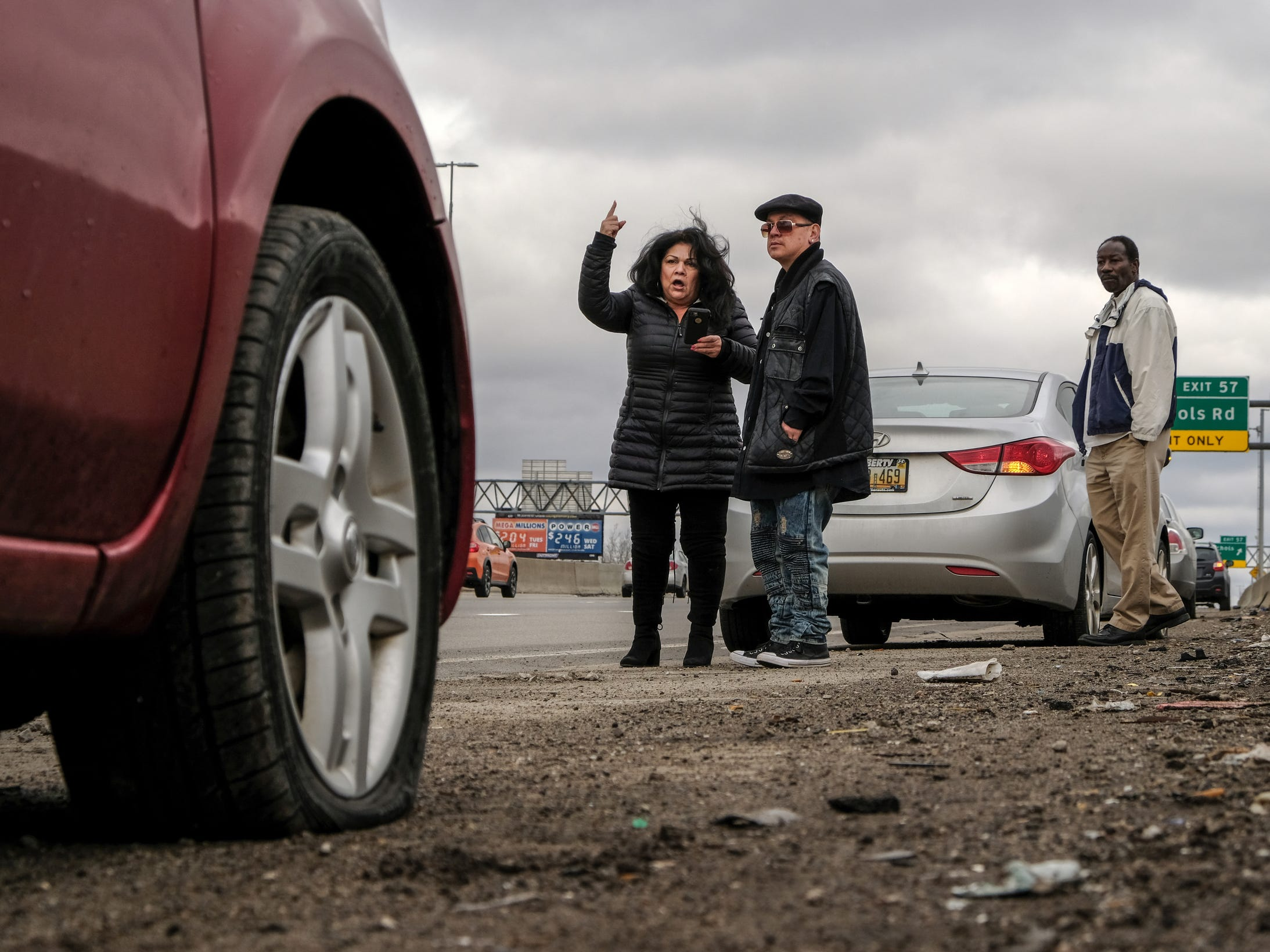 Sylvia Campos of Detroit gets upset while watching traffic from the side of northbound I-75 near the McNichols Rd. exit with her boyfriend Rolando Lopez of Saginaw after hitting a pothole that left her front passenger side tire flat on Wednesday, February 21, 2018 in Detroit.