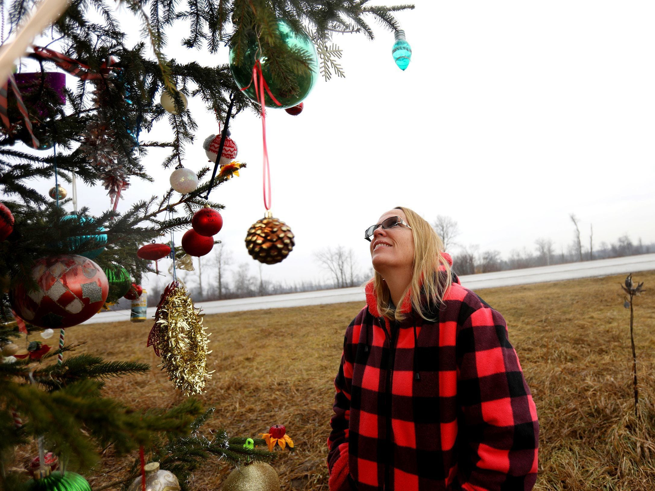 Kathy Porter looks at some of the new Christmas ornaments added since she last visited the Australian pine tree planted at the site of her son Jason's death, who was killed by a drunk driver 20 years ago. People driving by started adding Christmas ornaments throughout the years.