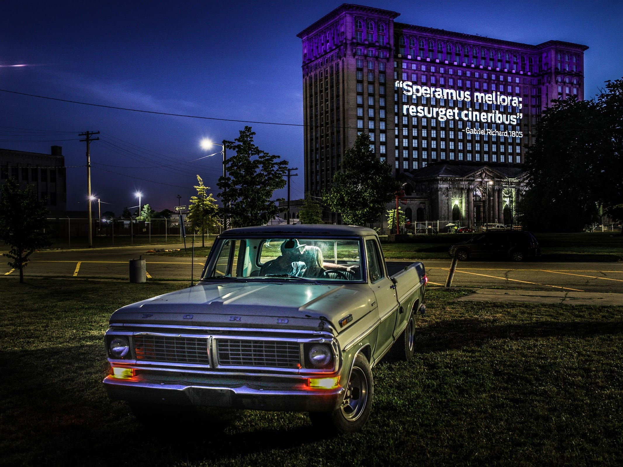"Cory Coffey and her husband Stephen McGee pose for a photograph sharing a kiss in her grand father's 1970 Ford Sport CUSTOM truck in front of the Michigan Central Station lit up with the two latin mottos written by Father Gabriel Richard after the fire of 1805, ""Speramus Meliora"" and ""Resurget Cineribus"" that translate as ""We hope for better things"" and ""It will rise from the ashes"" on Thursday, June 14, 2018. The couple was parked in front of their home facing the Michigan Central Station in Detroit."