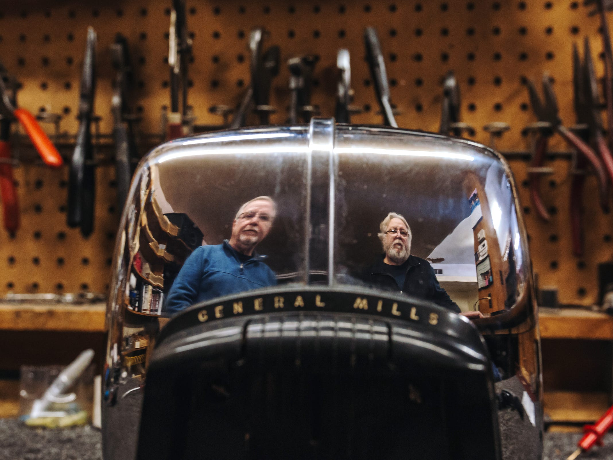 McNichols Electric co-owners Dave Kehoe (left) and his brother Pat Kehoe are seen reflected in an old General Mills toaster being repaired at their small appliance repair shop on Detroit's west side on Tuesday, March 20, 2018. The repair shop once had a dozen workers and four stores and is now down to the single location where the business was started by their father in 1953.