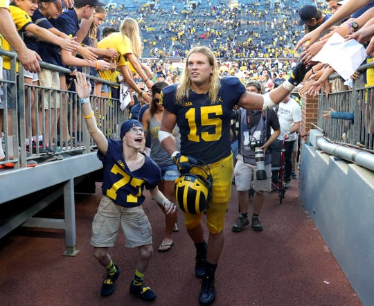 Michigan defensive lineman Chase Winovich and Larry Prout leave the field after the 45-20 win over SMU Saturday, September 15, 2018 at Michigan Stadium, in Ann Arbor, Mich.