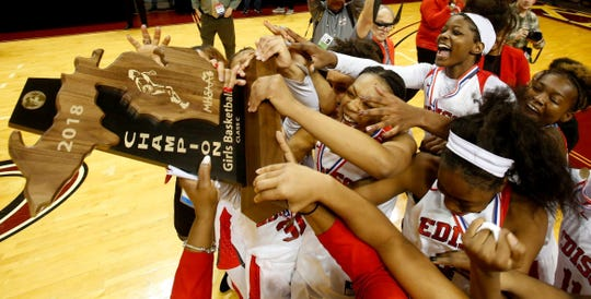 Detroit Edison celebrates with the Class C state trophy after Edison's 51-34 win in the Class C state final on Saturday, March, 17, 2018, in Grand Rapids.