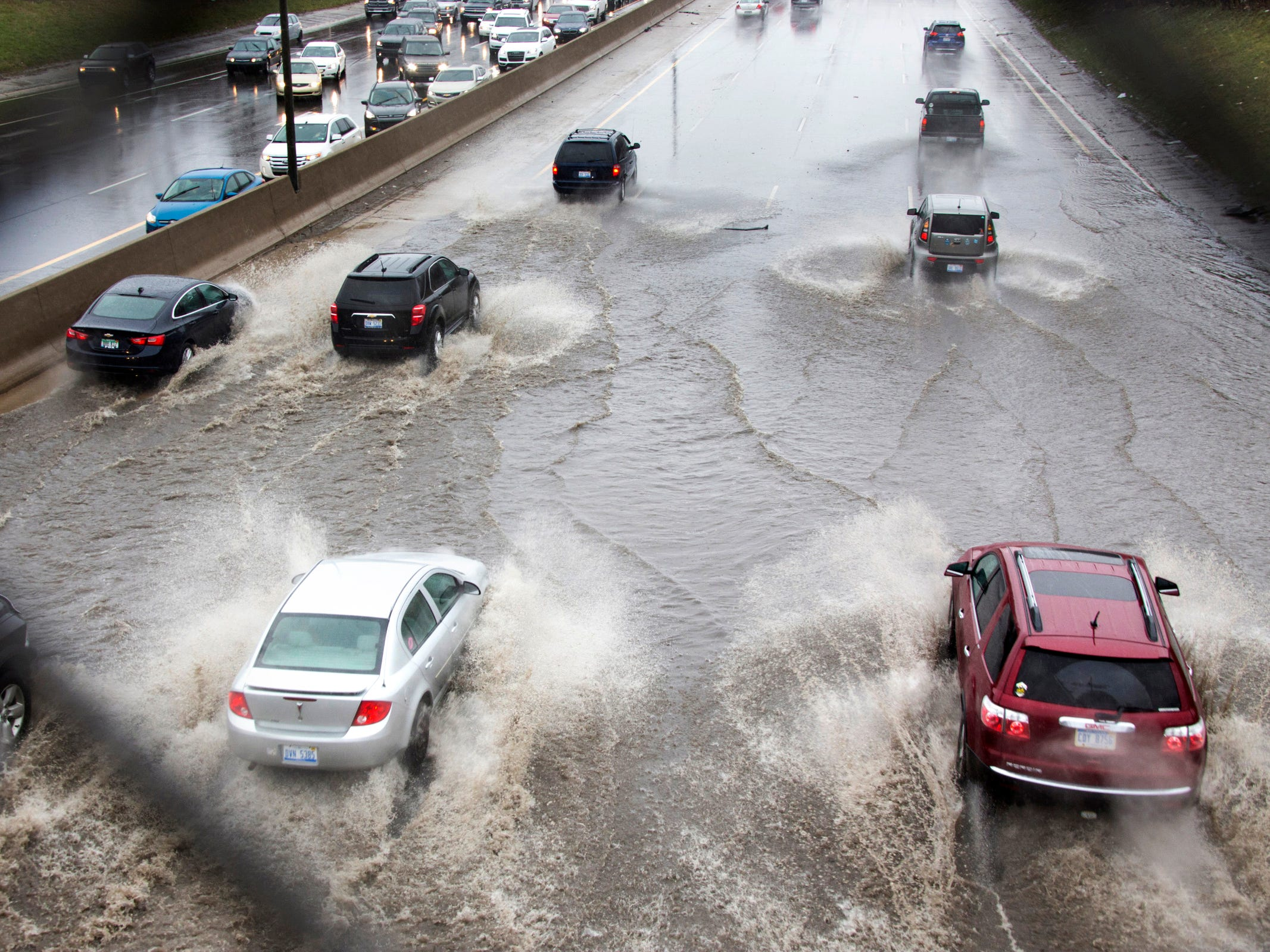 Cars drive under the 7 Mile overpass on I-75 through flooded waters in Detroit Sunday April 15, 2018.