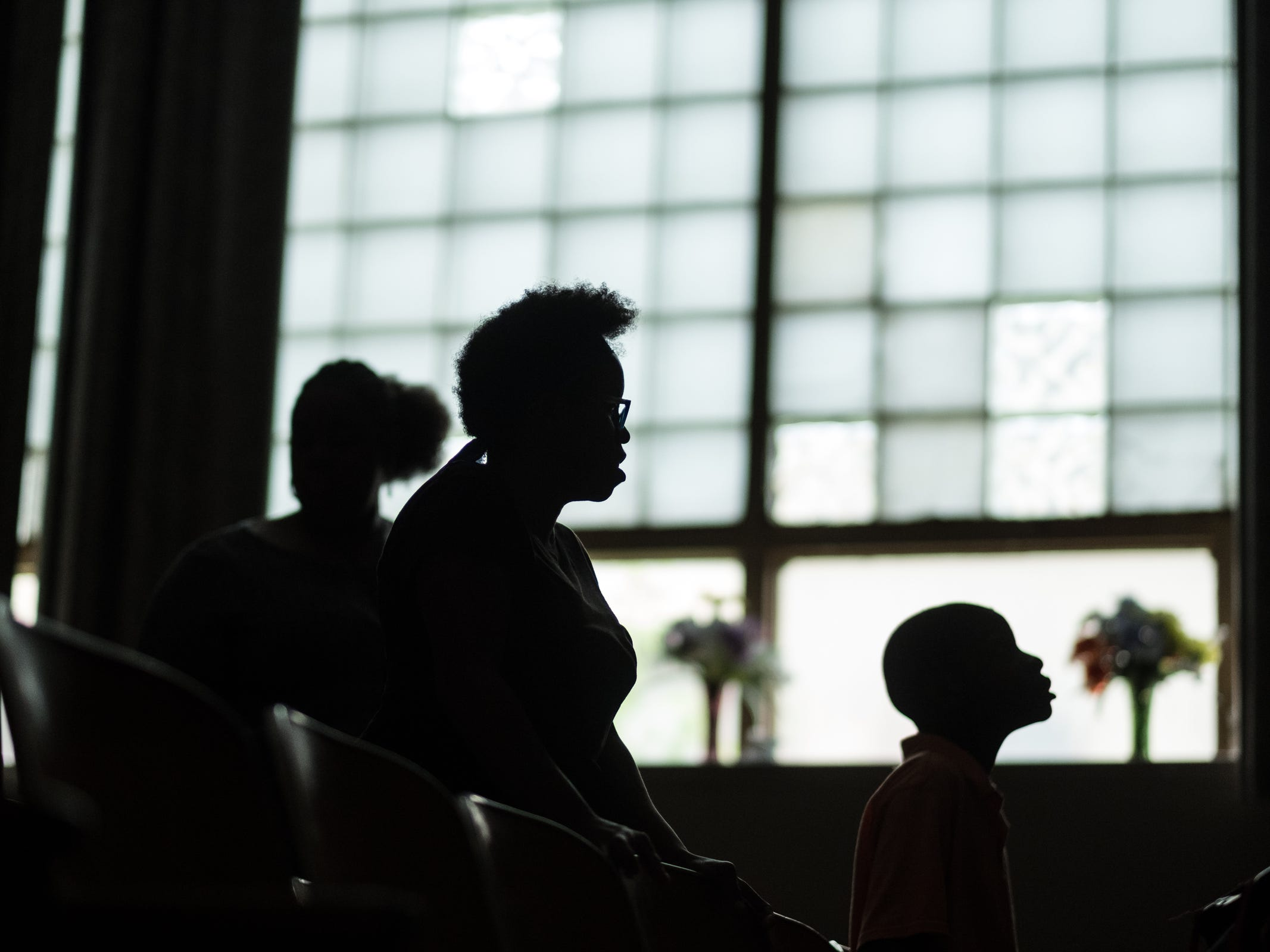 (right to left) Jakson Bell of Detroit, Nakisha Hale of Detroit and Katia Beasley of Detroit are silhouetted while listening to a church service performed by Apostle Michael Beasley on Saturday, June 23, 2018 at True Life Change Ministries in Detroit's west side.
