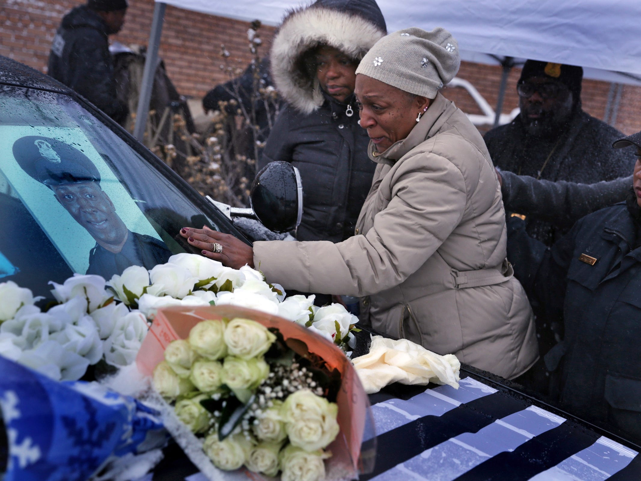 Nikole Flowers, center mourns the death of her son Detroit Police officer Glenn Doss at the end of a vigil at the 7th precinct in Detroit on Monday, January 29, 2017. Officer Doss died Sunday in the hospital days after being shot while responding to a domestic call on Detroit's east side.