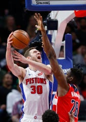 Detroit Pistons forward Jon Leuer (30) shoots against Washington Wizards center Ian Mahinmi (28) during the second half of an NBA basketball game Wednesday, Dec. 26, 2018, in Detroit. The Pistons defeated the Wizards 106-95.