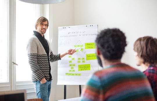 Businessman presenting his ideas on whiteboard to colleagues during a business presentation in boardroom