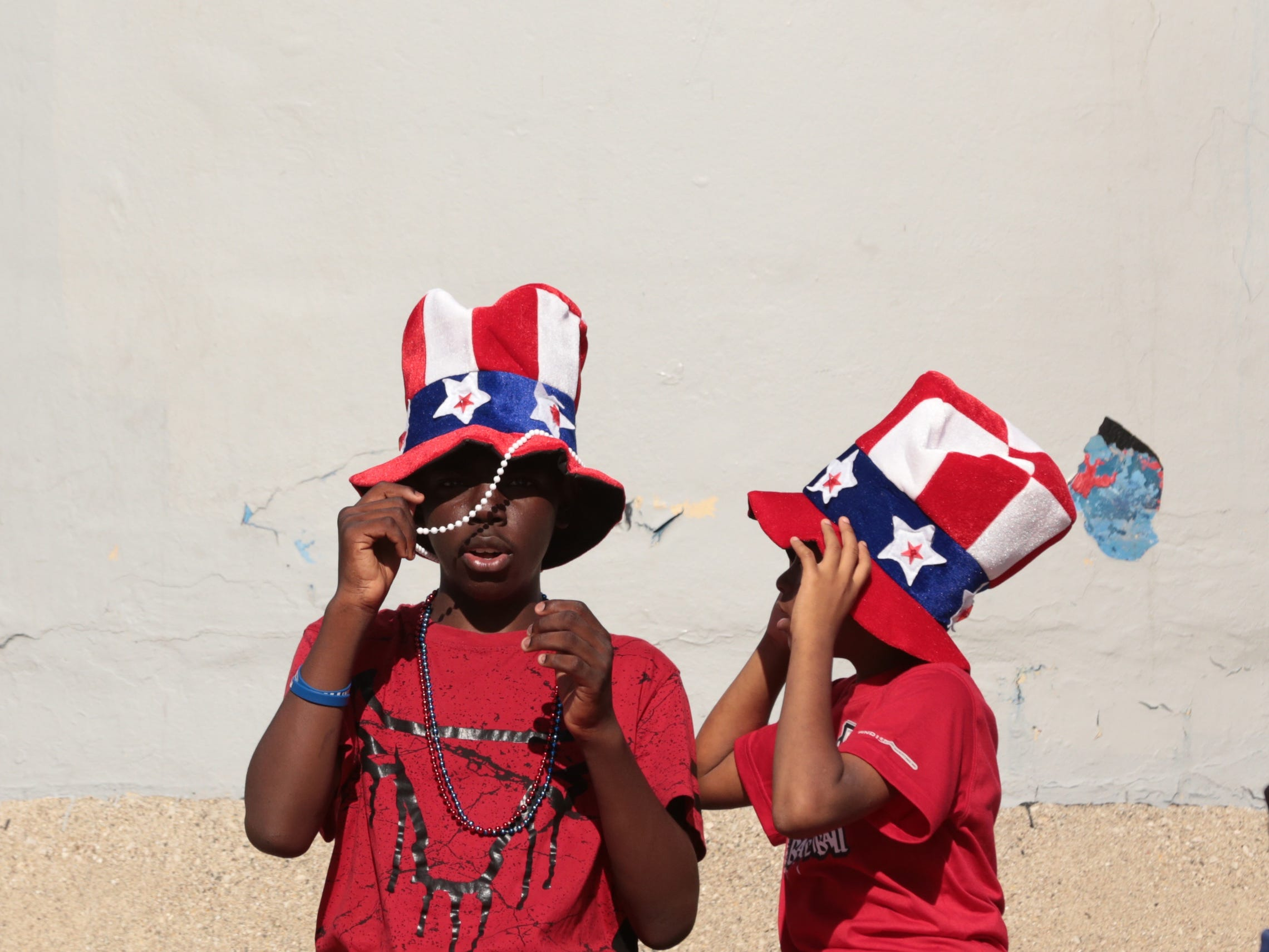 Elijah Wilson (left) of Detroit and his brother Ar'nez Gordon of Detroit wear matching hats while waiting for the start of the 2018 Ford Fireworks at Hart Plaza in downtown Detroit on Monday, June 25, 2018.