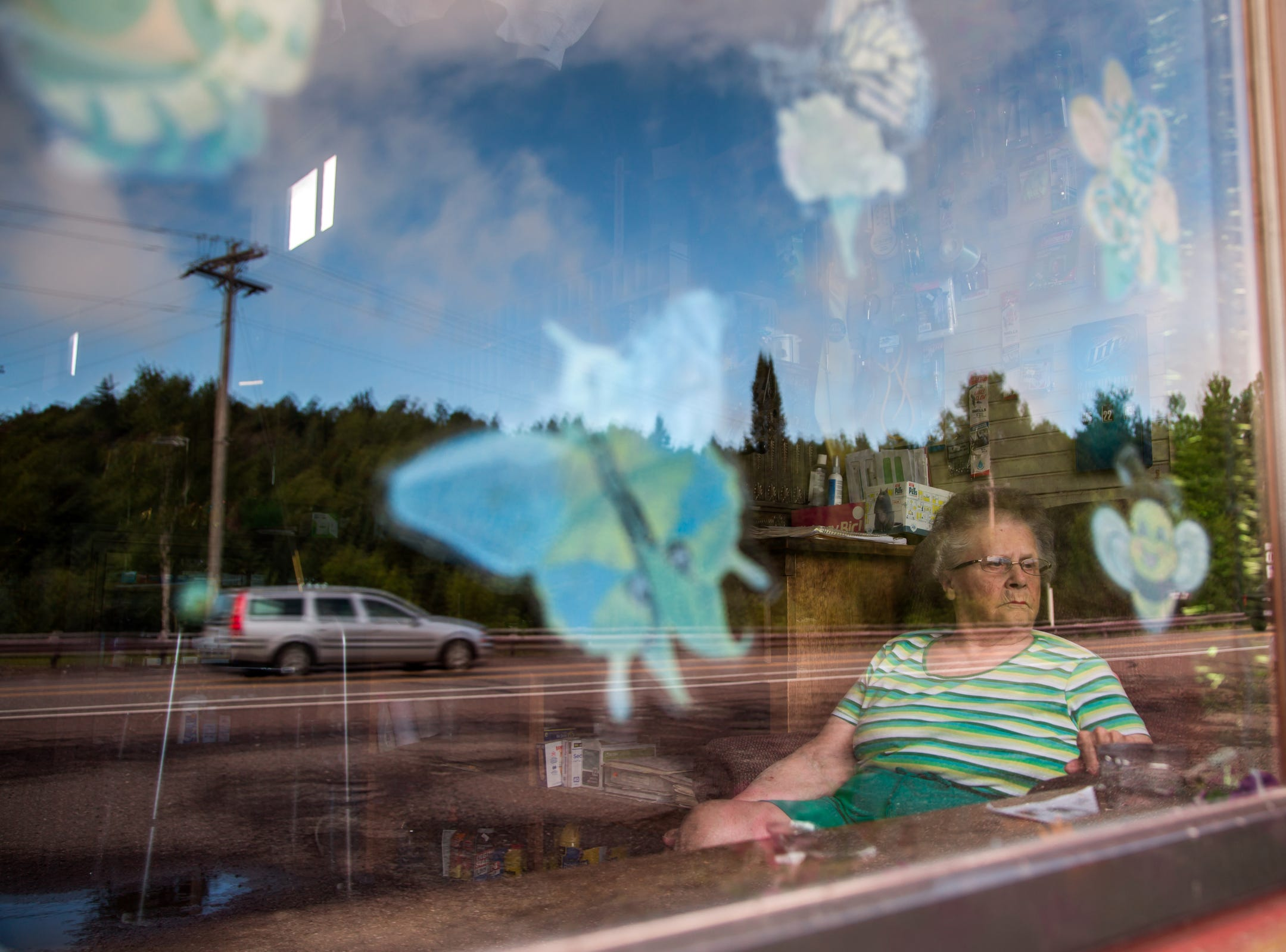 "Arbutus Peterson, 84, of Phoenix watches traffic go by outside of the old-fashioned general store named Phoenix Store built in 1873 that she runs by herself on Tuesday, August 22, 2017 in Michigan's Upper Peninsula.  Peterson spends eleven  hours-a-day seven days-a-week in her chair waiting for customers and waiving at those she knows as they pass by. ""I see people all day long so I don't think anything about living in a town with that few people in it,"" Peterson said who owns the only store in town."