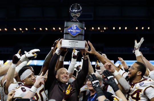 Minnesota head coach P.J. Fleck holds the champions trophy after the Quick Lane Bowl NCAA college football game against Georgia Tech, Wednesday, Dec. 26, 2018, in Detroit. Minnesota won 34-10.