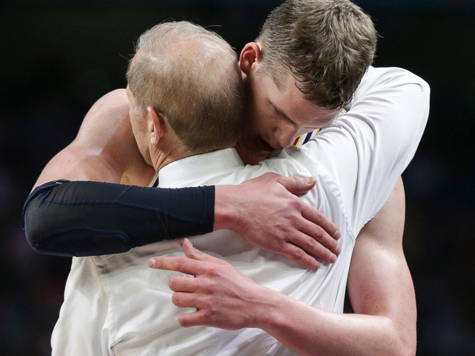 Michigan head coach John Beilein hugs Michigan forward Moritz Wagner (13) as he leaves the floor during the NCAA division 1 men's basketball national championship game between Michigan and Villanova on Monday, April 2, 2018, at the Alamodome in San Antonio.