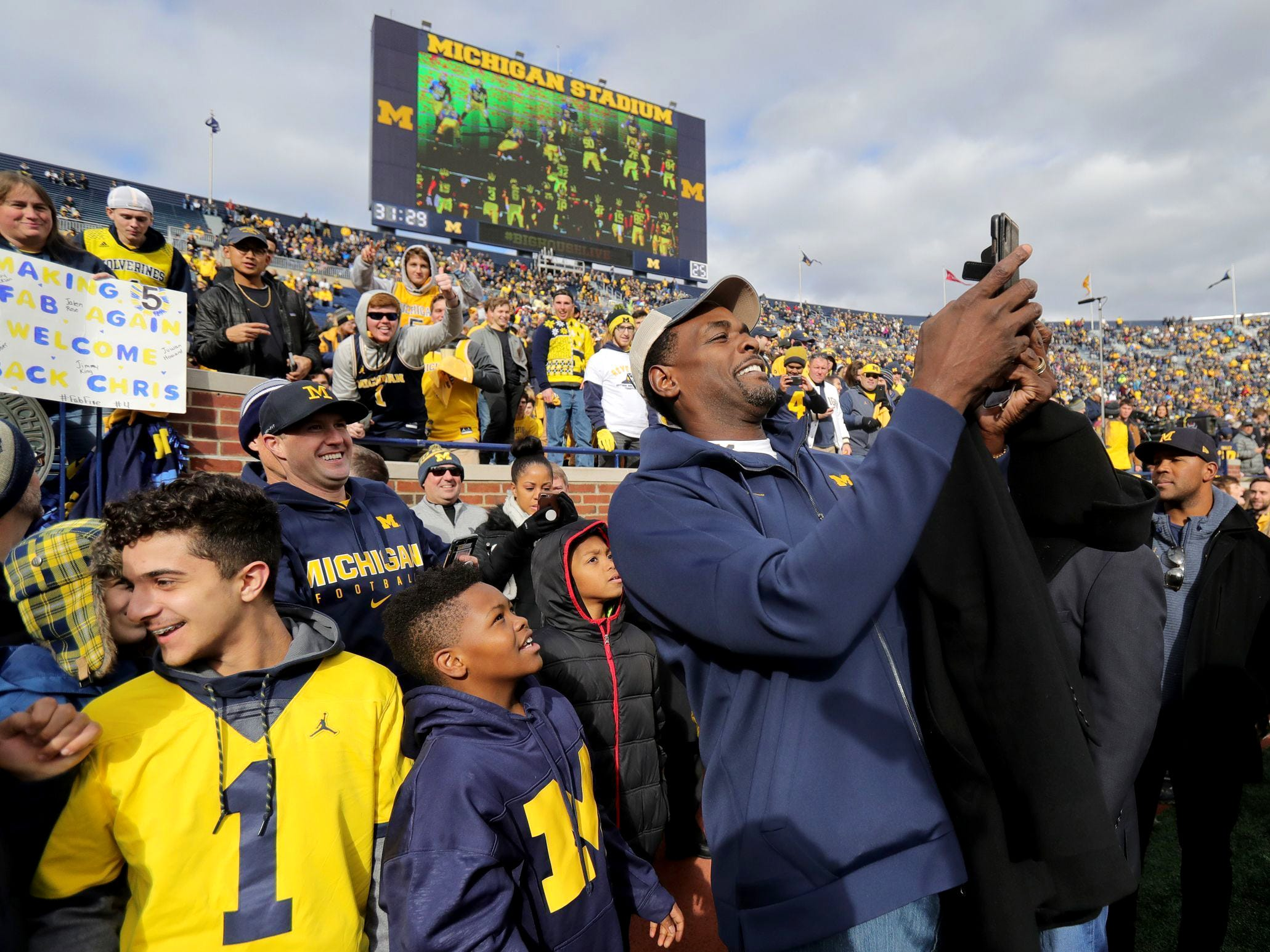Former Michigan basketball player Chris Webber takes a selfie with fans on the football field prior to the start of the Michigan and Penn State game on Saturday, Nov. 3, 2018, at Michigan Stadium.