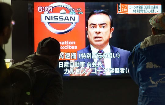 Pedestrians look at a television screen showing a news program featuring former Nissan chief Carlos Ghosn in Tokyo on December 21, 2018.