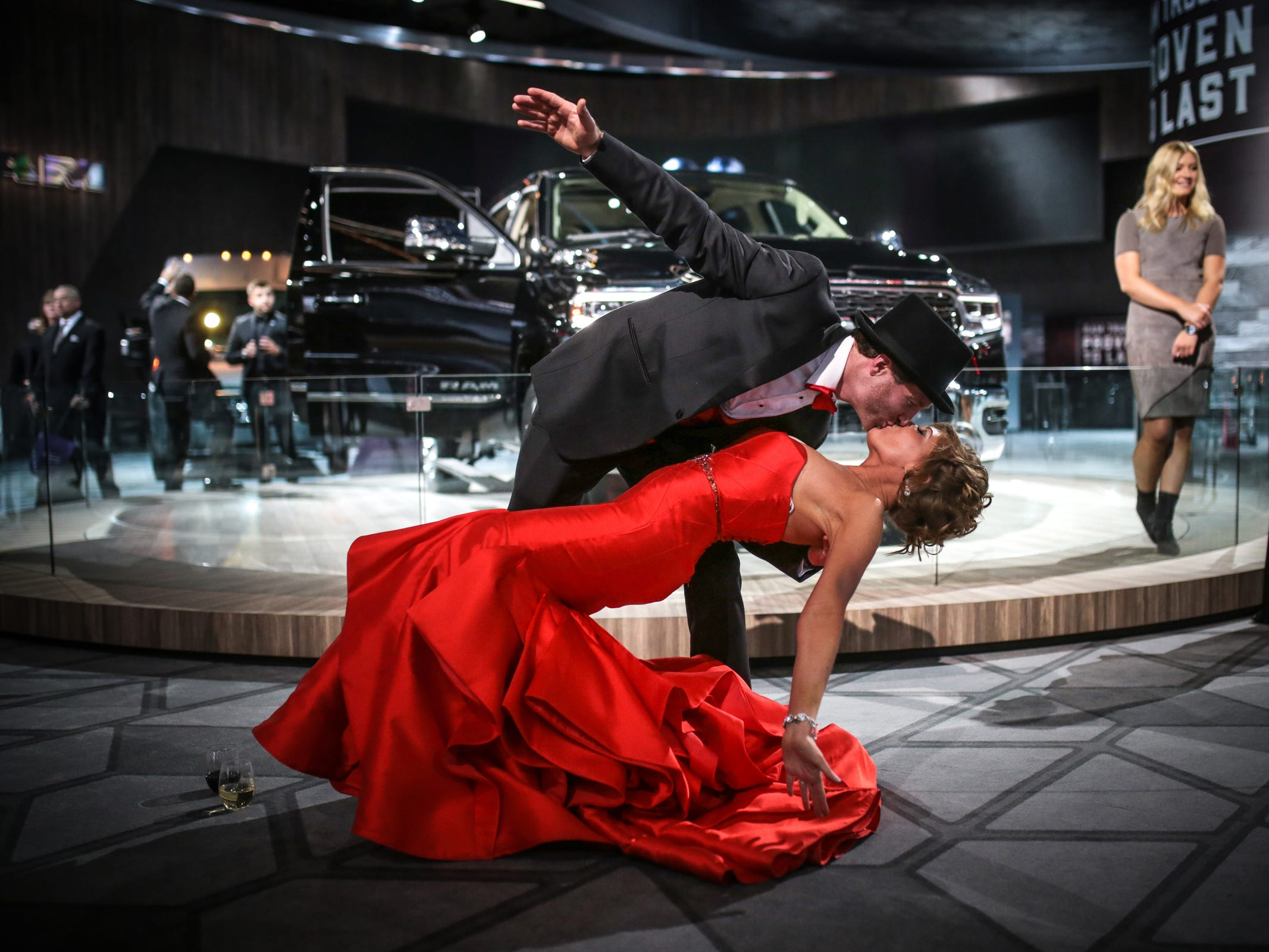 Greg Schmidt of Newaygo dips his fiancee Marie Anderson of Southfield in front of Ram 1500 Limited during the 2018 North American International Auto Show Charity Preview at Cobo Center in downtown Detroit on January 19, 2018.