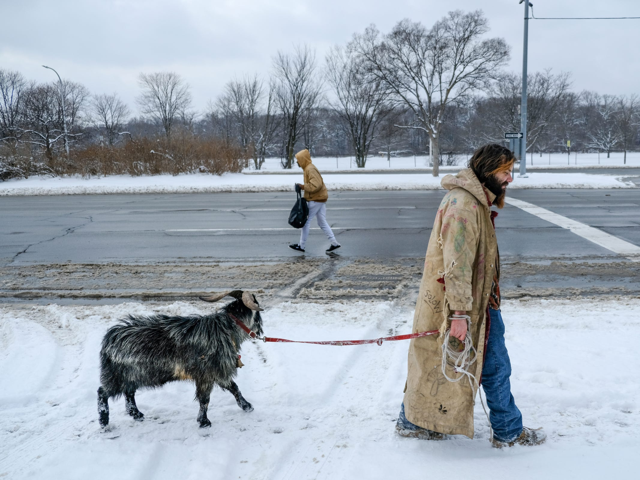 Erick Brown, 31, of Detroit walks with his goat named Deer along Woodward Ave. in Detroit on Wednesday, February 7, 2018. Brown was nearly beaten to death by people he let stay with him. The couple that set their dog on him and tied him up during the beating have since fled the state.