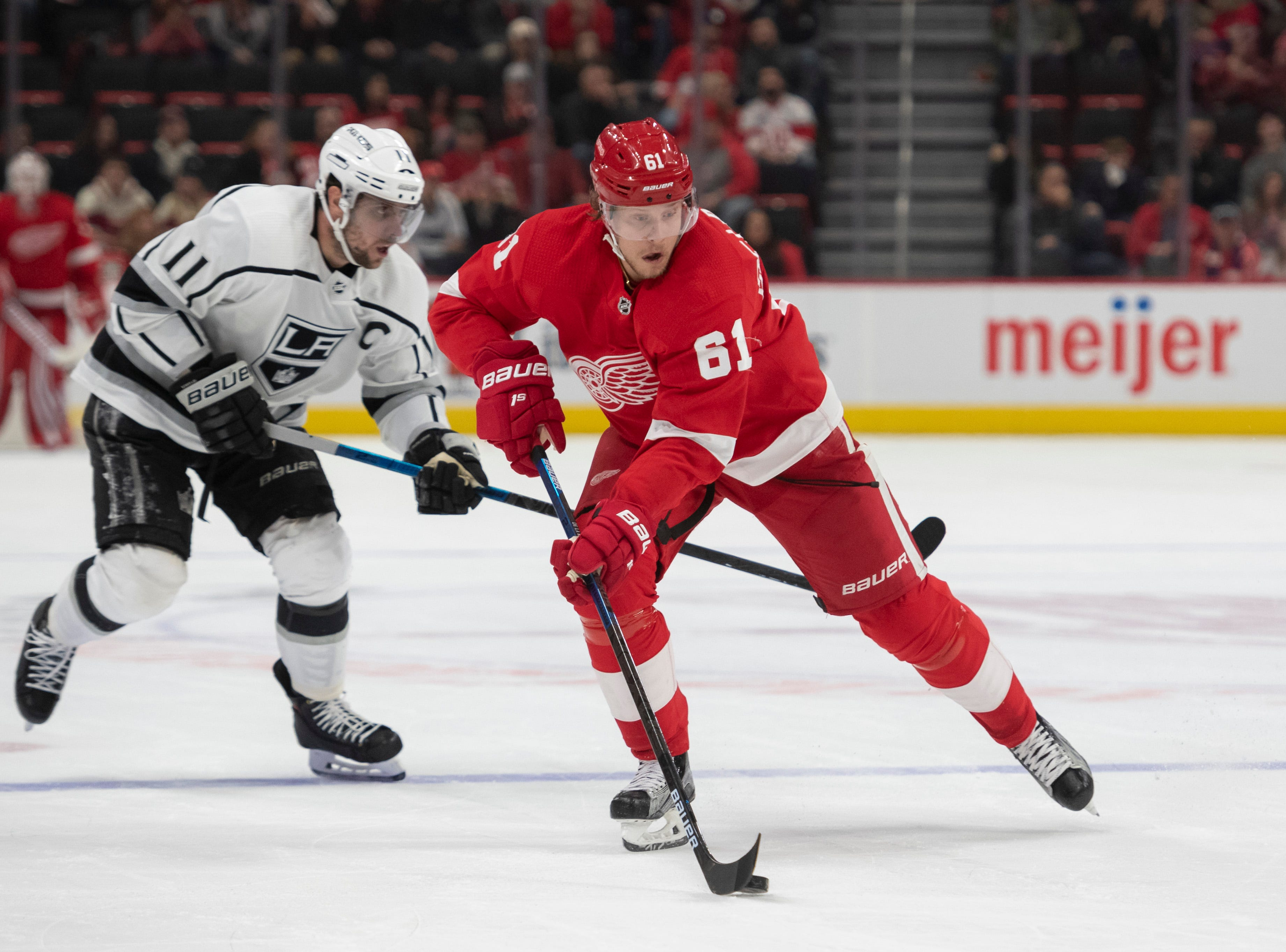 Detroit left wing Jacob De La Rose moves the puck away from Los Angeles center Anze Kopitar in the third period.               Photos are of the Detroit Red Wings vs. the Los Angeles Kings, at Little Caesars Arena, in Detroit, December 10, 2018.  (David Guralnick / The Detroit News)