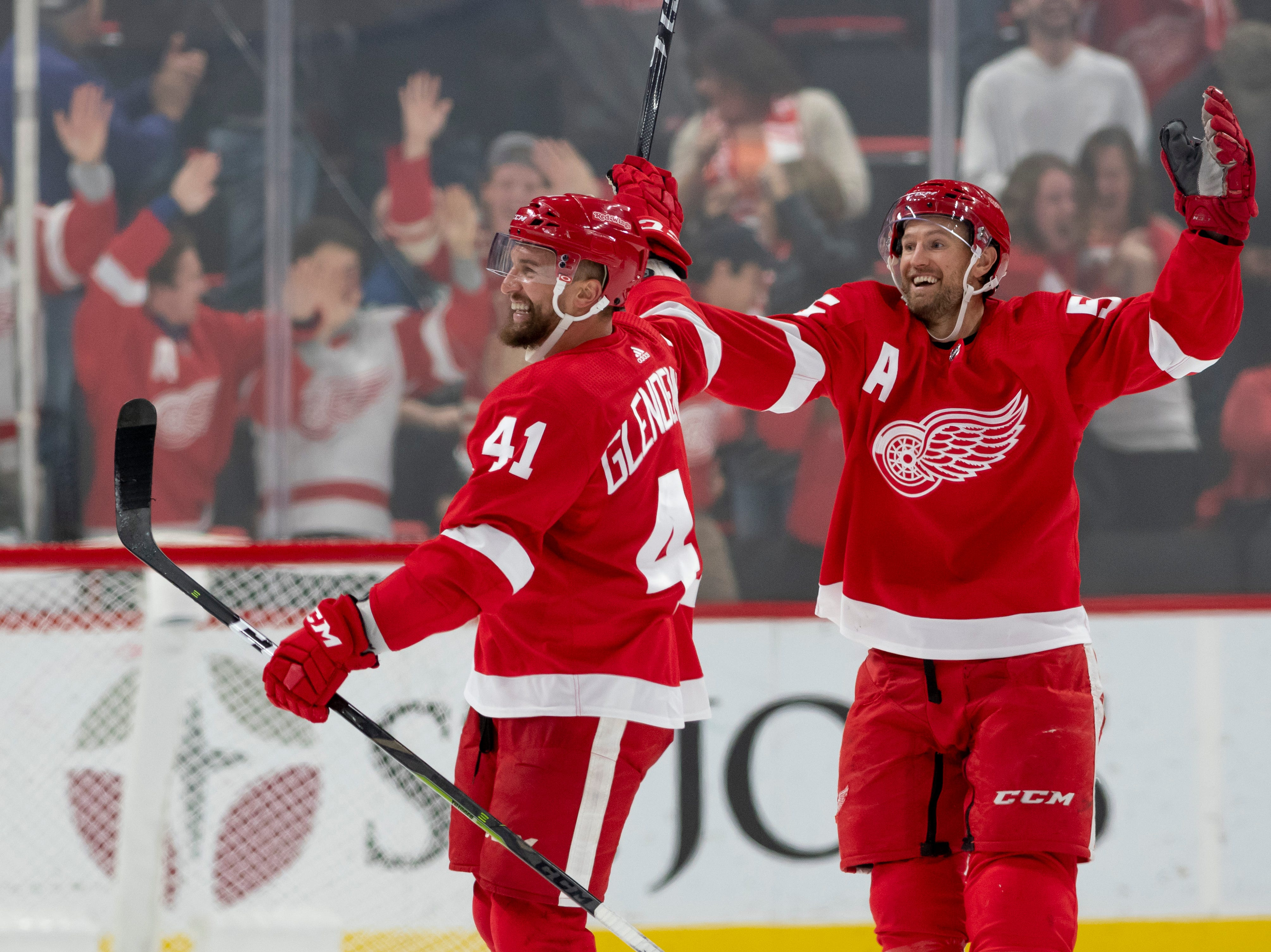Detroit center Luke Glendening, left, and defenseman Niklas Kronwall celebrate an short-handed empty net goal by defenseman Trevor Daley (not pictured) late in the third period.            Photos are of the Detroit Red Wings vs. the New Jersey Devils, at Little Caesars Arena, in Detroit, November 1, 2018.  (David Guralnick / The Detroit News)