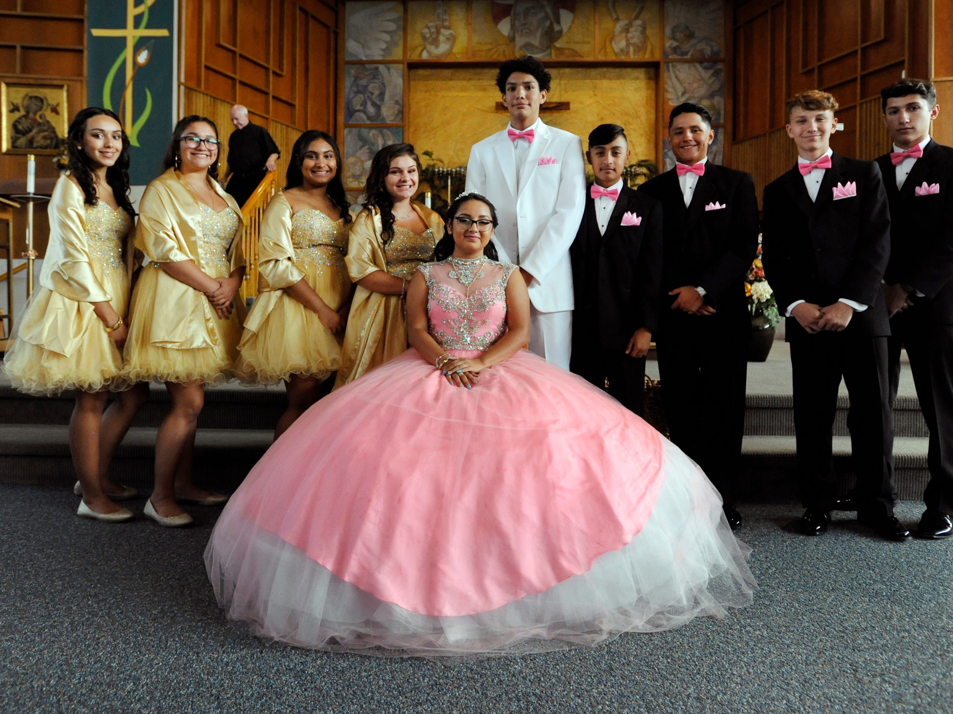 Soleil Garcia, center, sits for group photos with her court of honor at the conclusion of her quinceañera Mass.