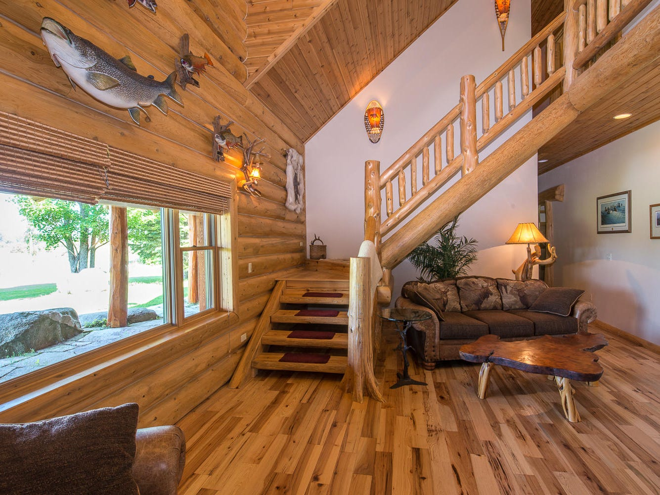 This 9,500-square-foot log home for sale in Sault Ste. Marie is listed at $2.25 million and features two fireplaces and a horse barn, and sits on 380 acres of meadows, hay fields and pastures. In addition to its views of woods, meadows and fields, 1.5 miles of the Charlotte River runs through the property. Built in 2001, this two-story, single-family house has five bedrooms, five bathrooms, a great room with a 36-foot vaulted ceiling and a boulder fireplace that has twin cascading waterfalls.