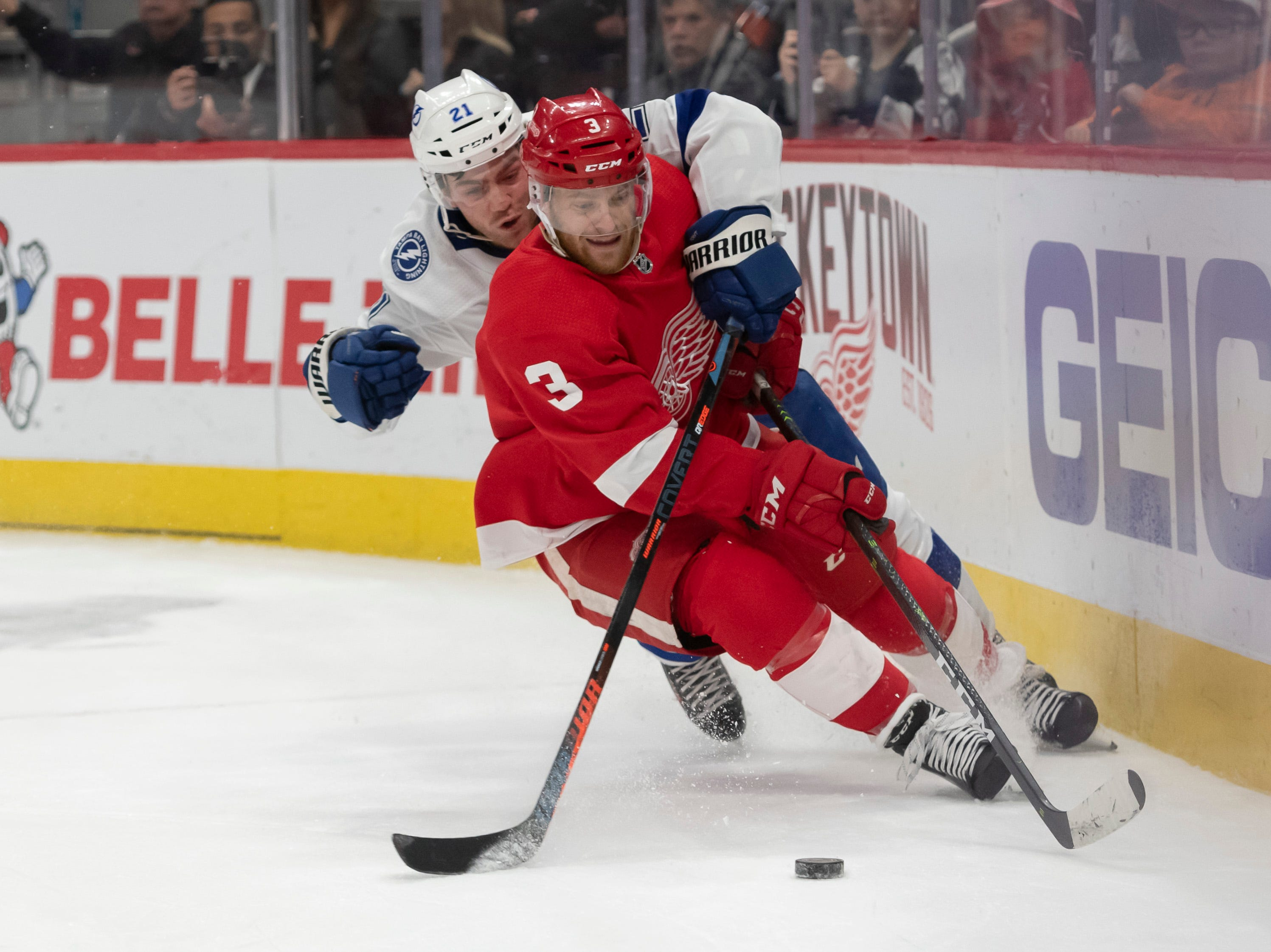 Detroit defenseman Nick Jensen and Tampa Bay center Brayden Point hit the ice while battling for the puck in the second period.             Photos are of the Detroit Red Wings vs. the Tampa Bay Lightning, at Little Caesars Arena, in Detroit, December 4, 2018.  (David Guralnick / The Detroit News)