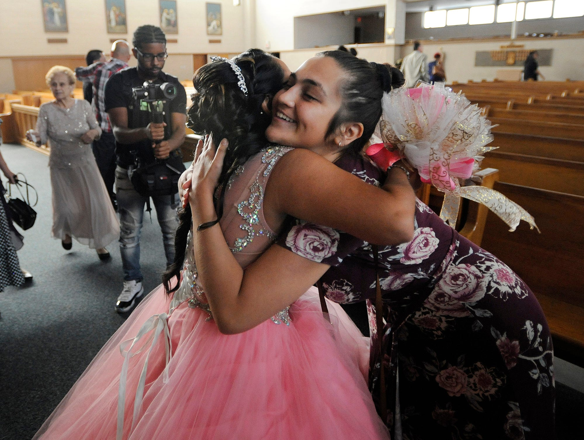 Soleil Garcia, left, is hugged by cousin Esperanza Gonzalez at the conclusion of her quinceañera Mass.